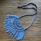 Necklace made of yarn laying on a wooden flat surface.  Necklace color is a light gray called Silver for the tie and half circle with the fringe being a light blue called Sky.  Necklace design is half circle made with textured stitches and fringe hanging from the edge around.