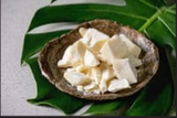 Image of pieces of cocoa butter in a brown bowl on a wide green leaf
