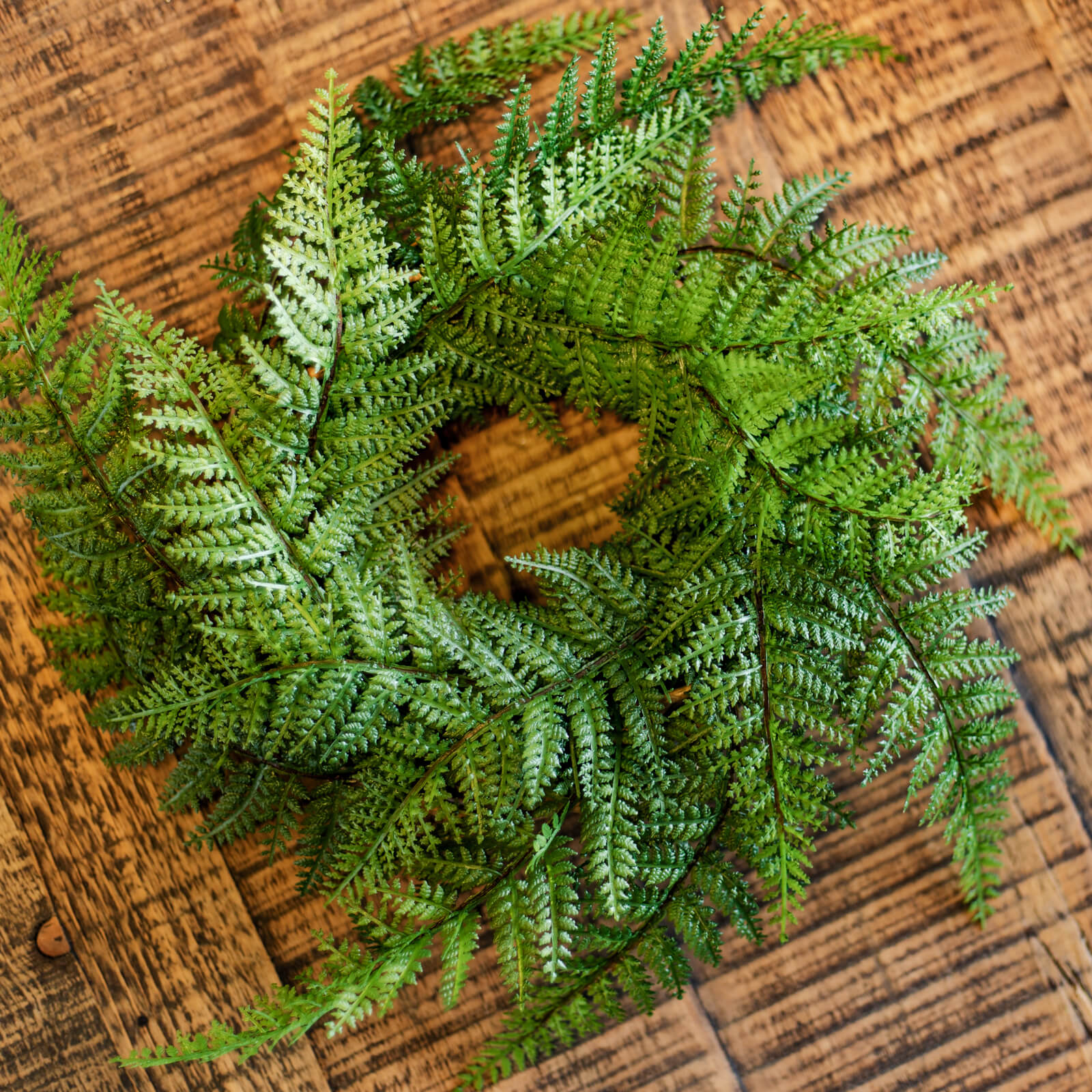 A gorgeous spring greenery wreath made of faux wispy fern leaves, resting on a wooden table new Olathe, Kansas.