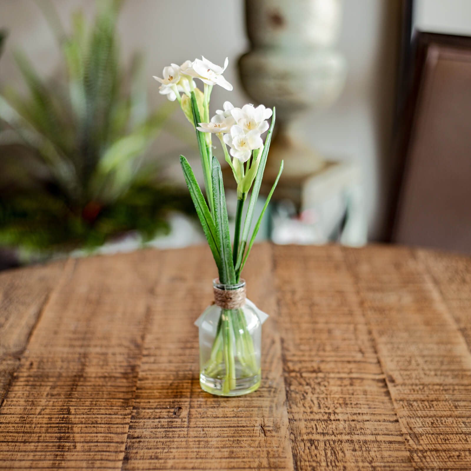 A small, beautiful spray of faux Narcissus in a small clear glass jar with natural twine around the neck. Resting in the sunshine on a table by the window.