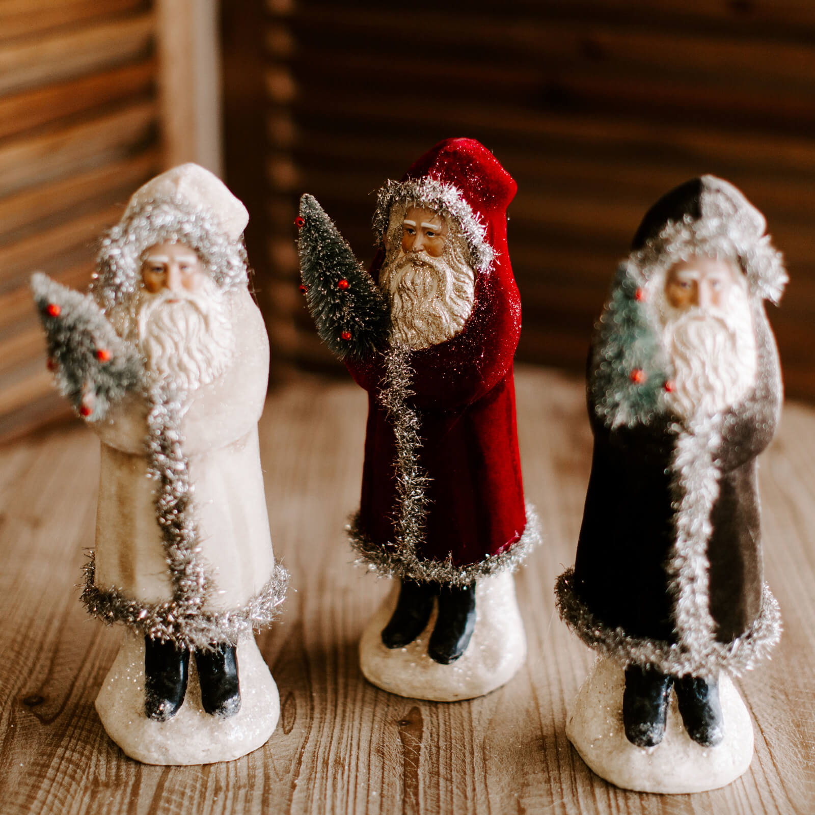 Three 12 and half inch Belsnickle figurines, one with a white coat, one with a red coat and one charcoal coat with tinsel trim and light glitter details