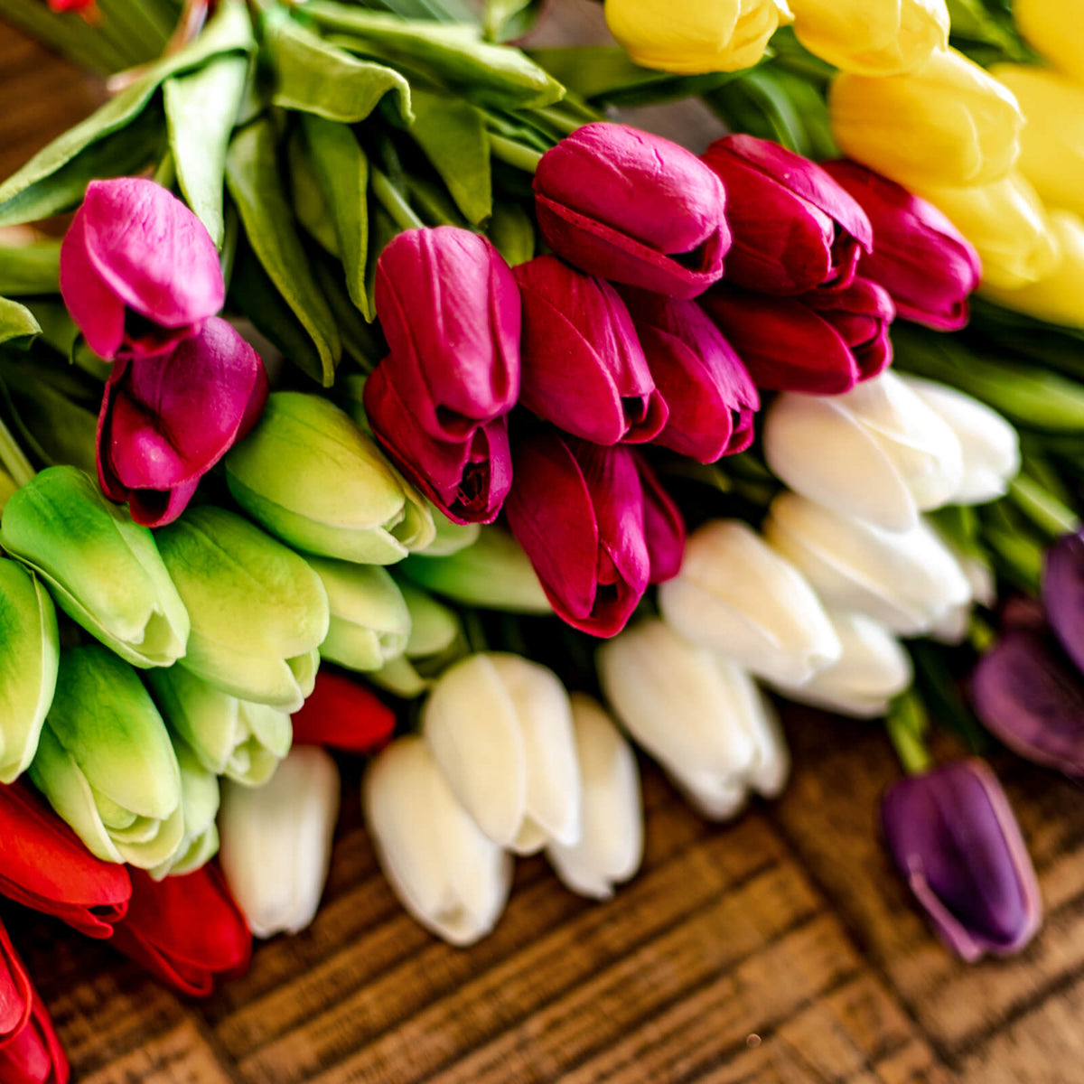 Very realistic faux tulips in yellow, red, green white, purple and pink piled high on a table in the Kansas City area of Topeka, Kansas