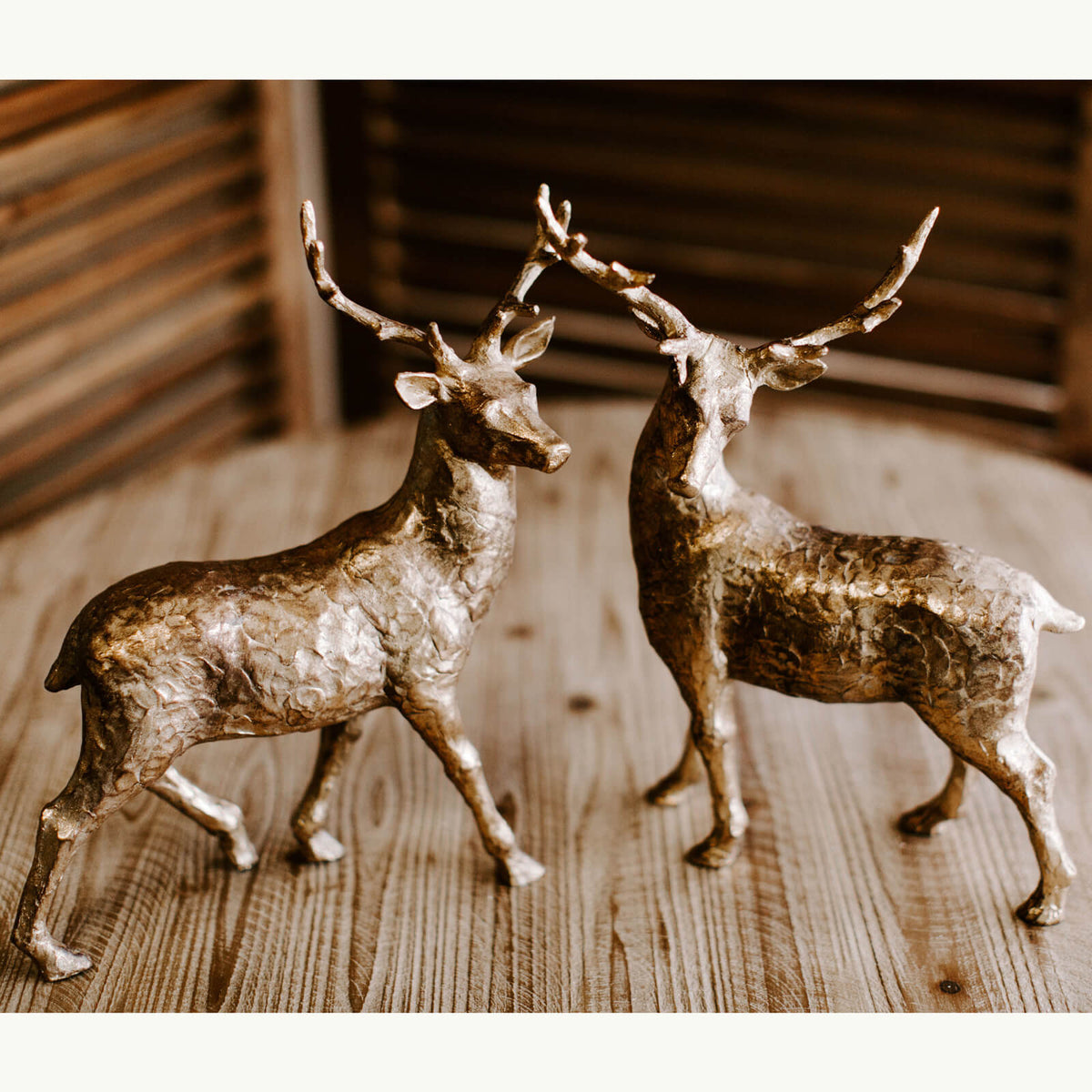 Two majestic fourteen and a half inch tall deer in gold with antlers. One on the left walking forward and the one on the right turning his head to the left.