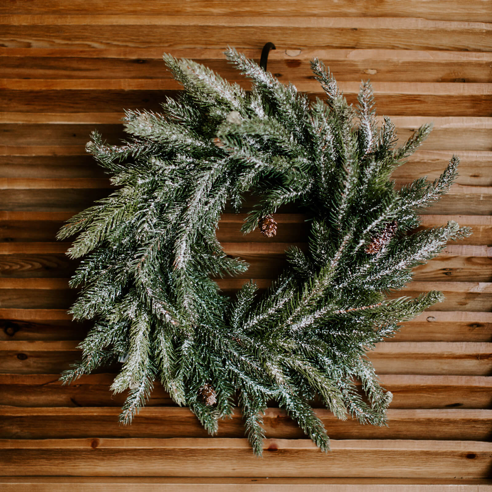 A 17 inch faux frosted pine wreath dusted in faux snow and adorned with real pinecones, hung on a wooden door for the holidays