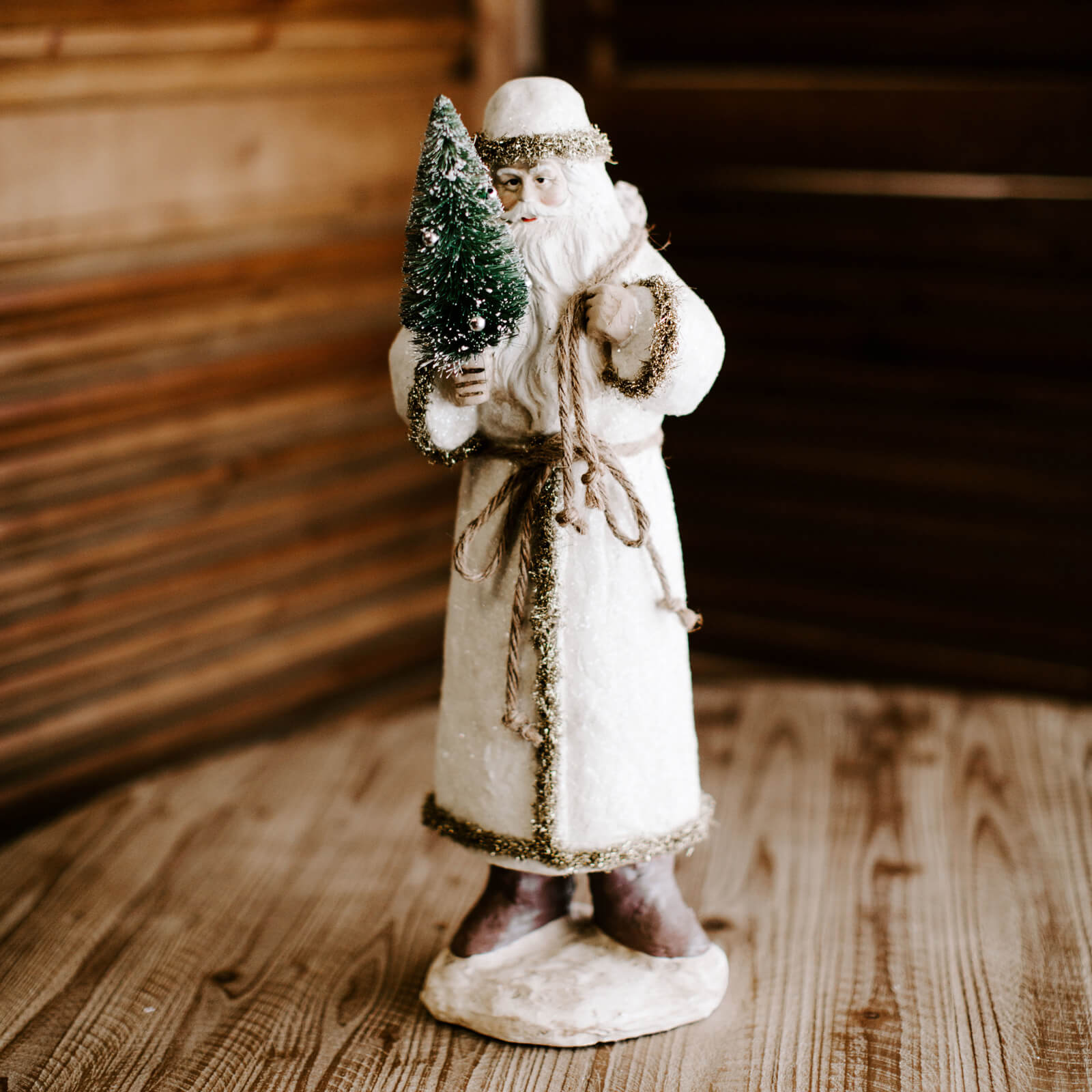 An 18 inch tall paper mâché santa figurine in a white coat with gold glittery trim, holding a small green tree, with a soft smile on his face for Christmas decorating