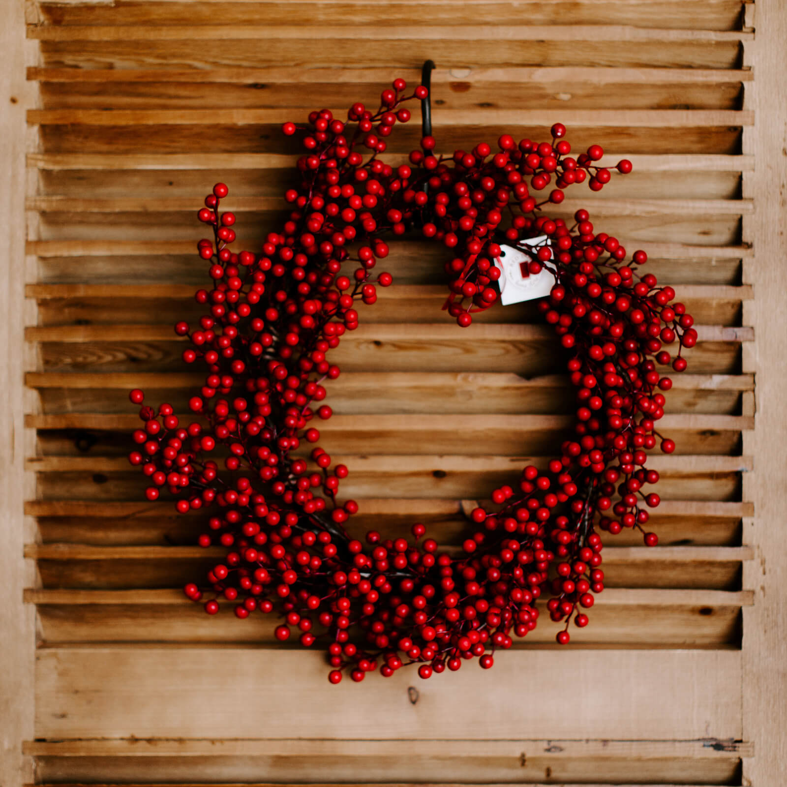An 18 inch matte, bright red faux berry wreath hung on a wooden door for holiday decorating.