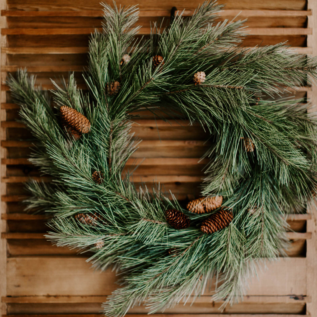 A 24 inch diameter soft faux pine wreath with real natural pinecones, a traditional winter decor wreath