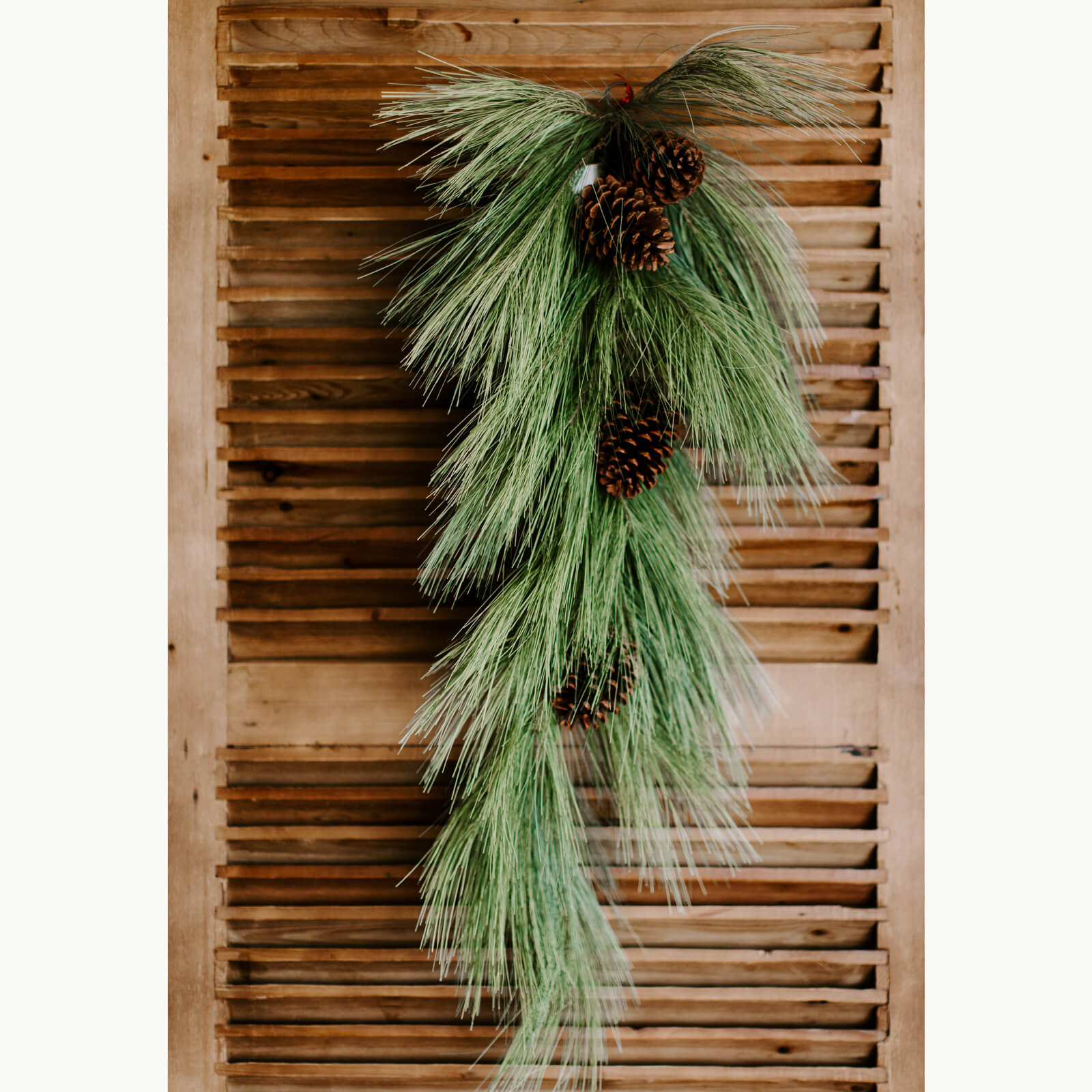 Realistic 36 inch long faux pine swag with long needles and pinecones hung on a door