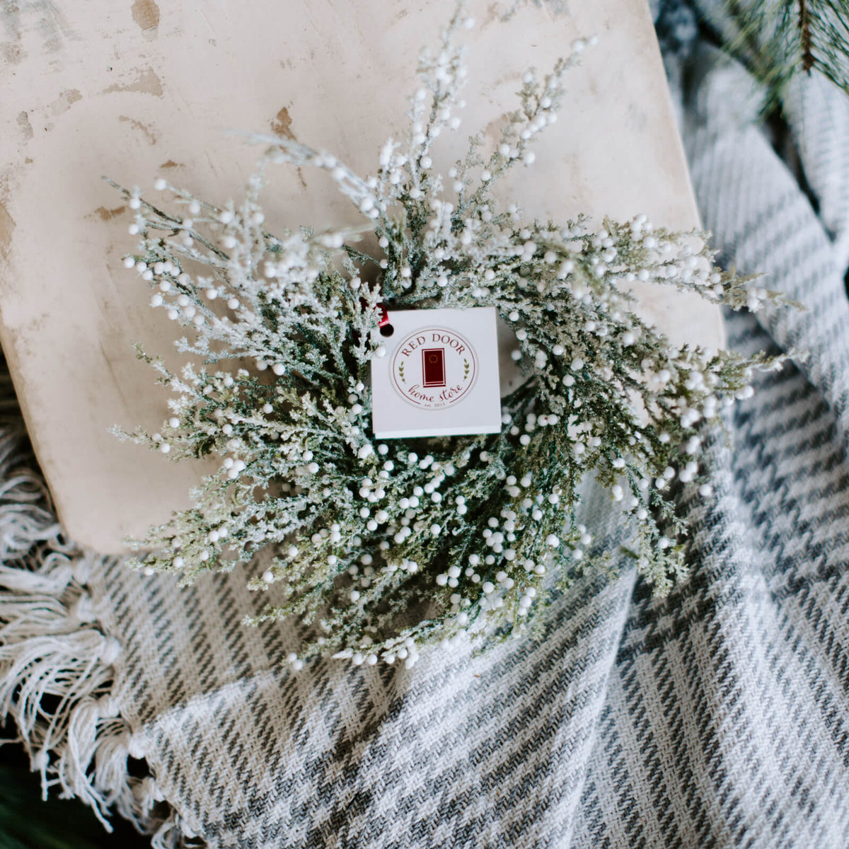 A small 3 inch diameter faux frosted berry wreath with snow covered cedar branches and lots of tiny white berries rest on a plaid blanket for holiday decorating