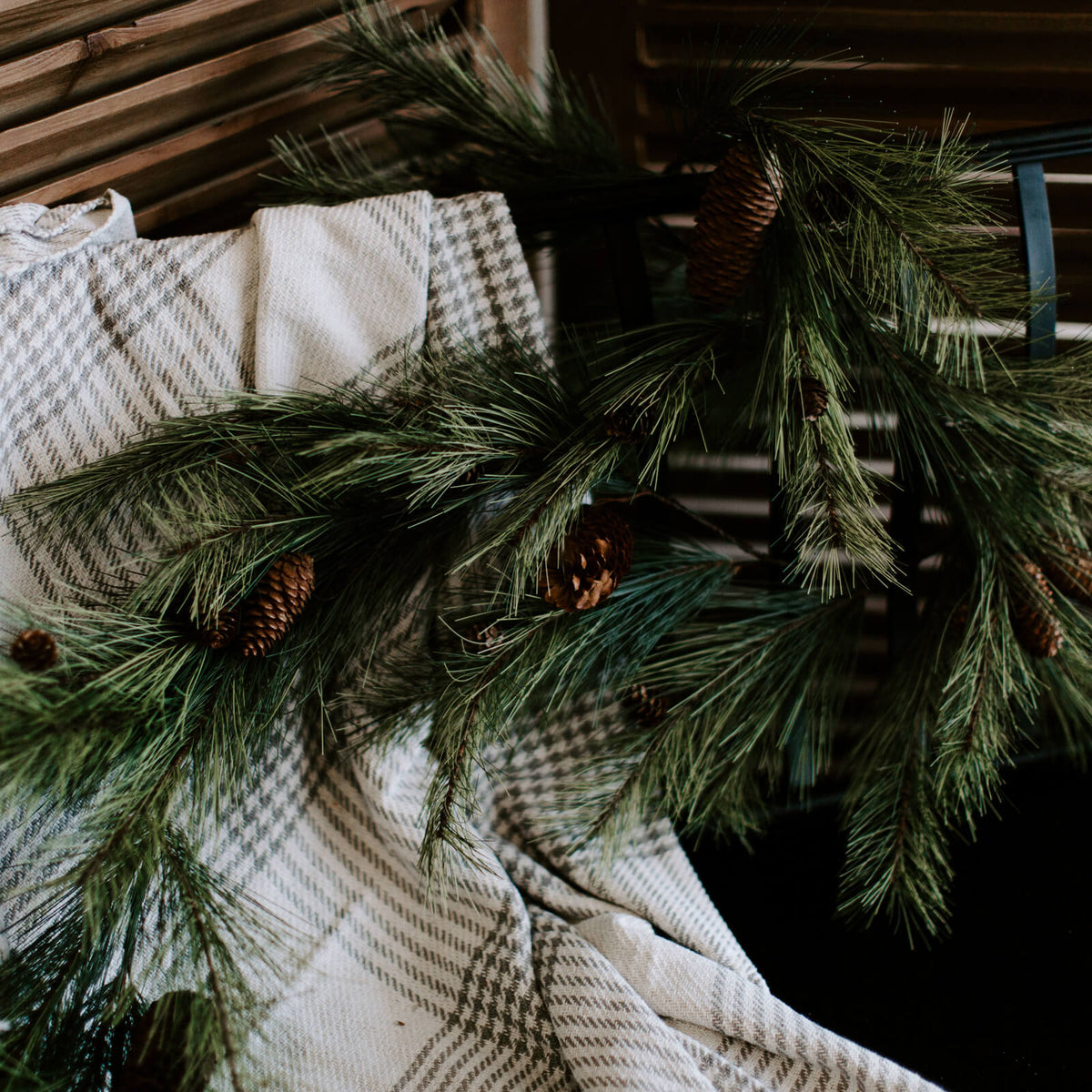 natural-looking faux 6 foot soft pine garland draped on entryway bench for holiday decorating
