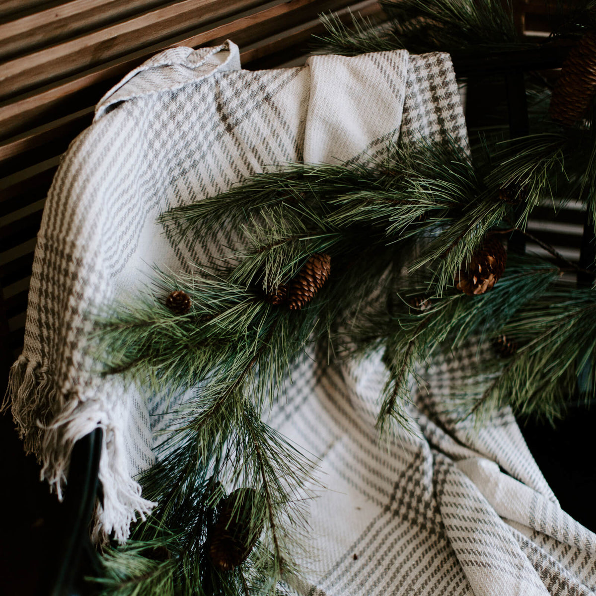closeup of natural-looking faux 6 foot soft pine garland adorned with pinecones and draped across an entryway bench for holiday decorating