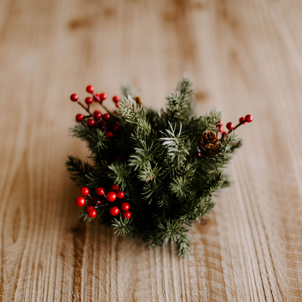Small half sphere of faux spruce and accents of red berries and mini pinecones resting on a rustic wooden table