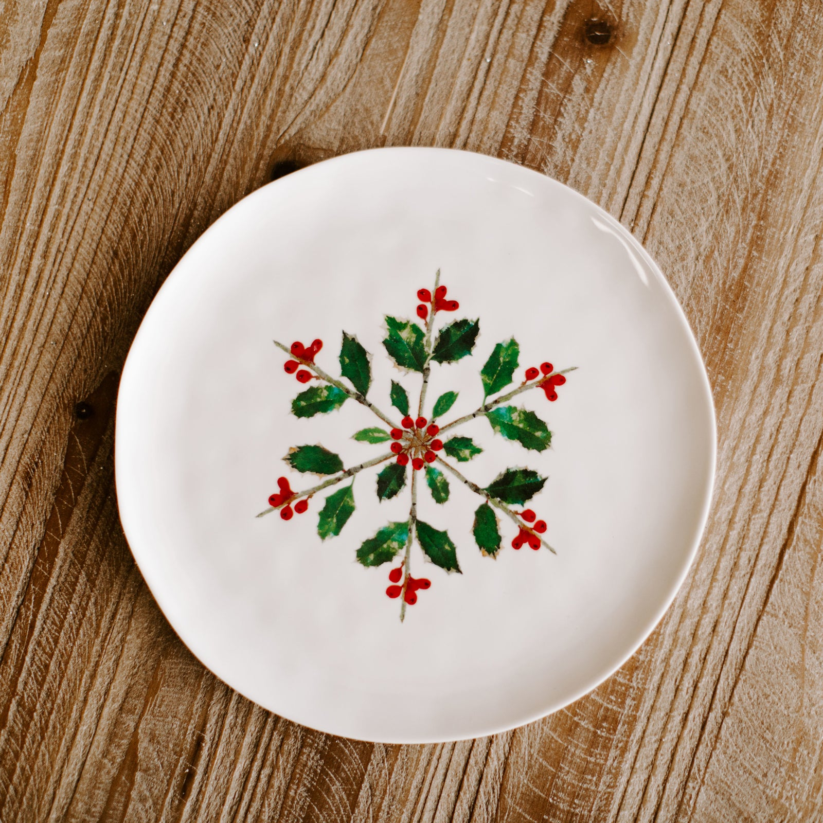 A 9 inch diameter winter plate with a pattern of twigs, Holly leaves and berries forming a snowflake type of pattern resting on a Christmas dinner table
