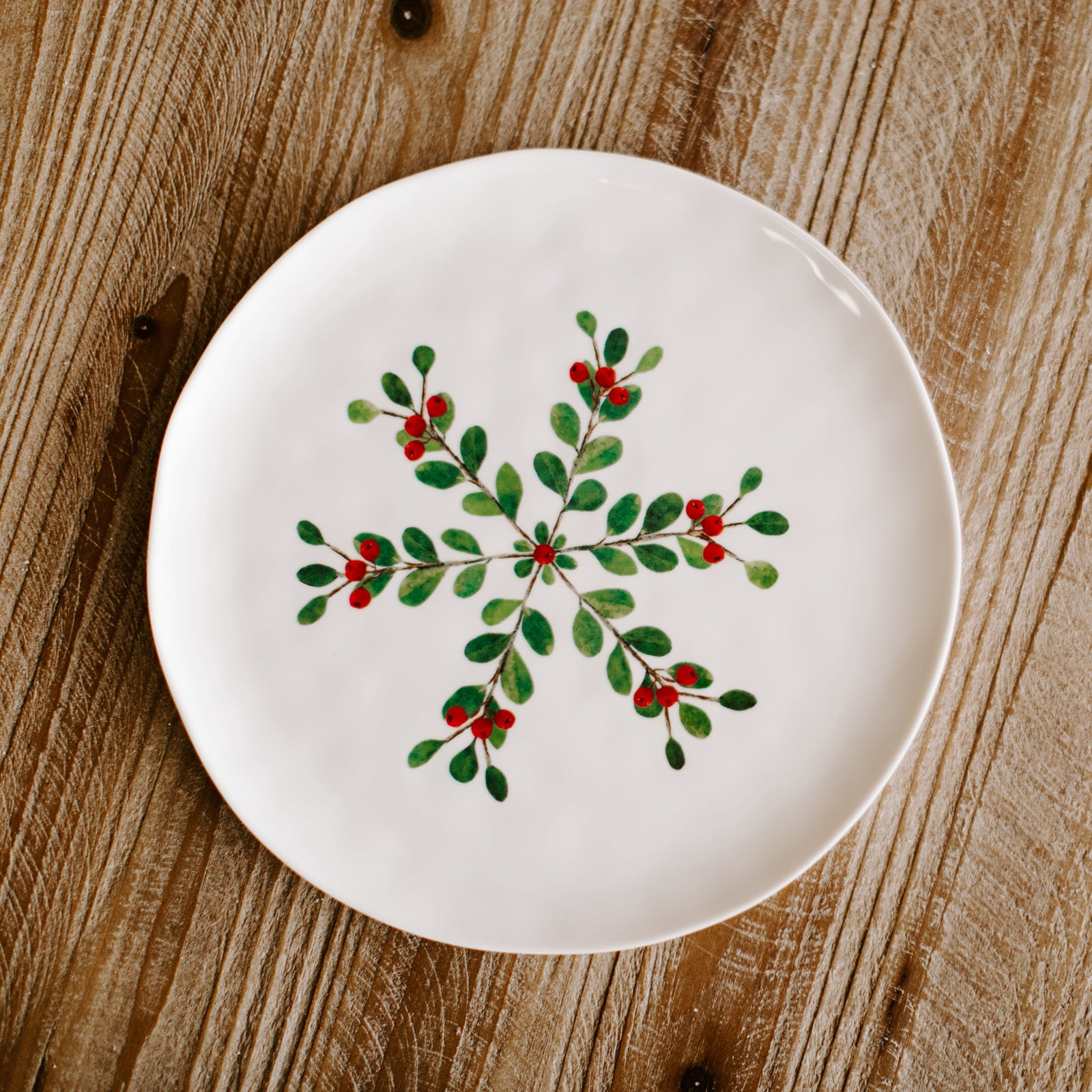 A 9 inch diameter winter plate with a pattern of twigs, light green leaves and berries forming a snowflake type of pattern resting on a holiday dinner table