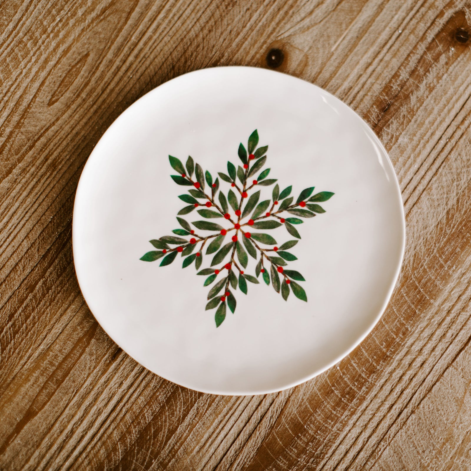 A 9 inch diameter winter plate with a pattern of dark green leaves and berries forming a snowflake type of pattern resting on a Christmas dinner table