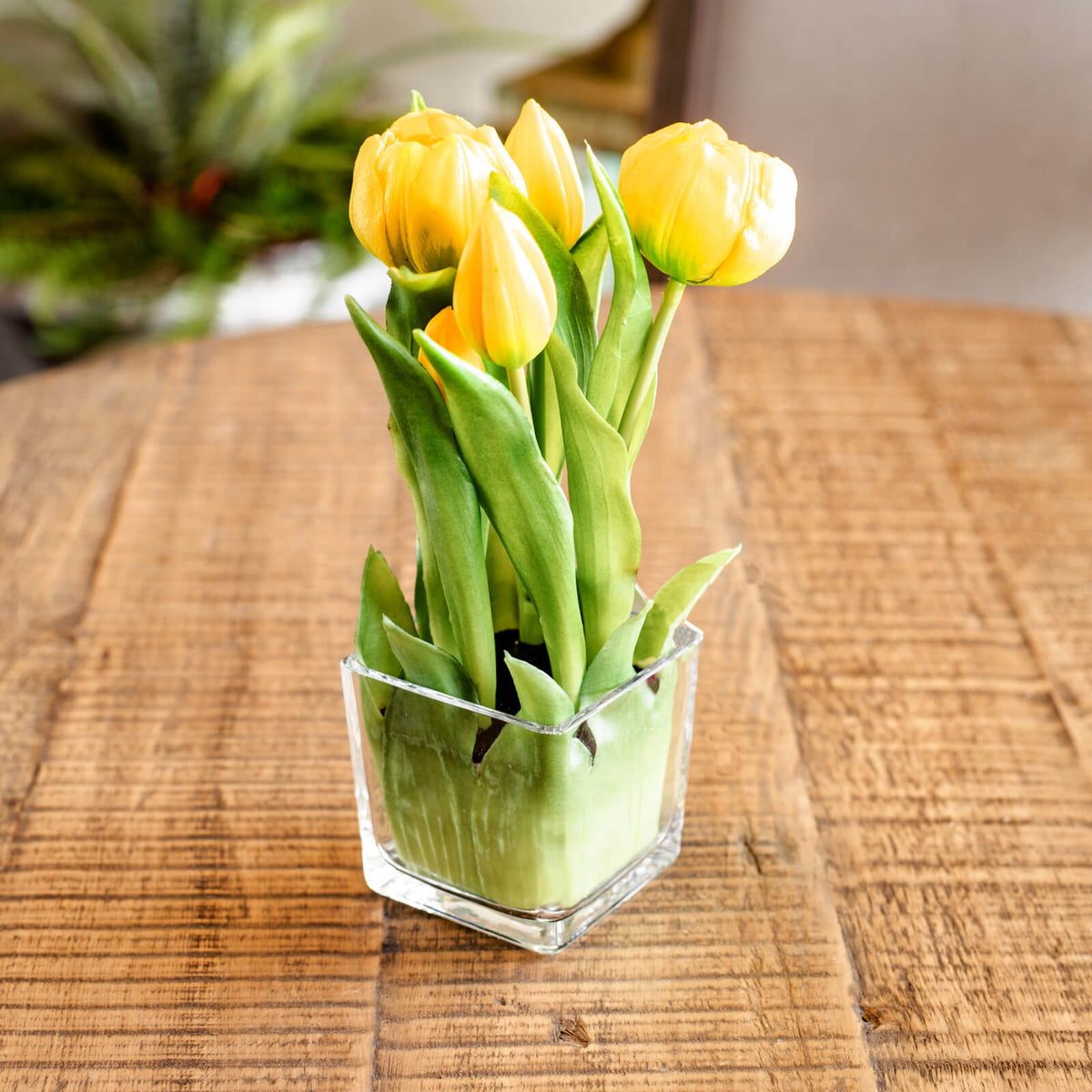 Very realistic looking faux yellow tulips resting on a table.