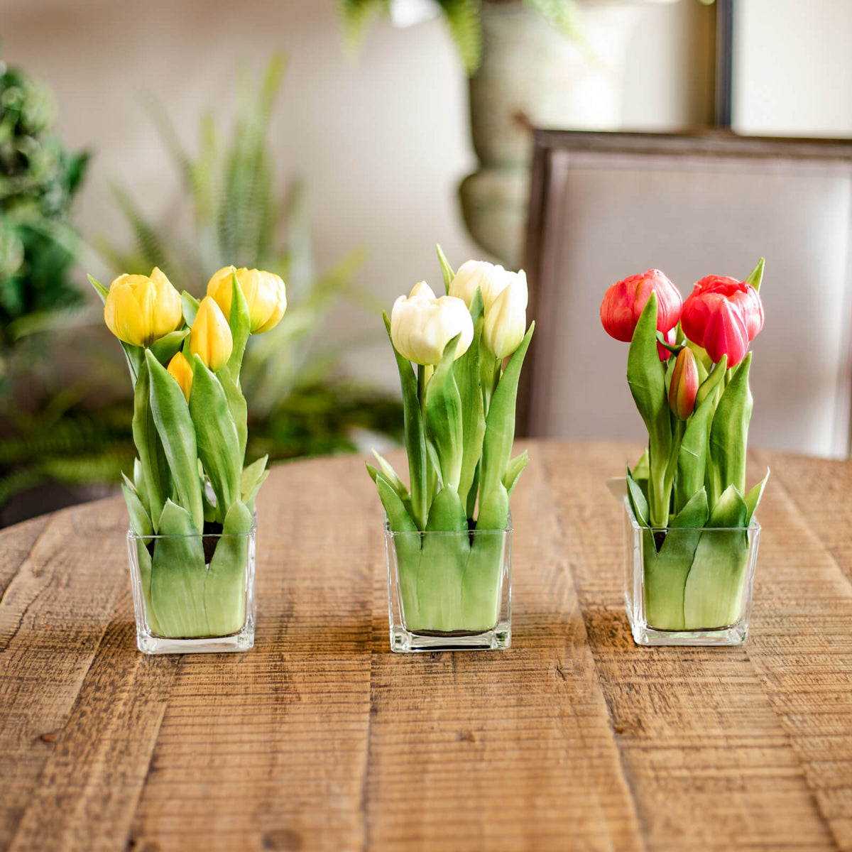 Luxury realistic faux yellow, white and pink tulips in clear glass containers on a tabletop.