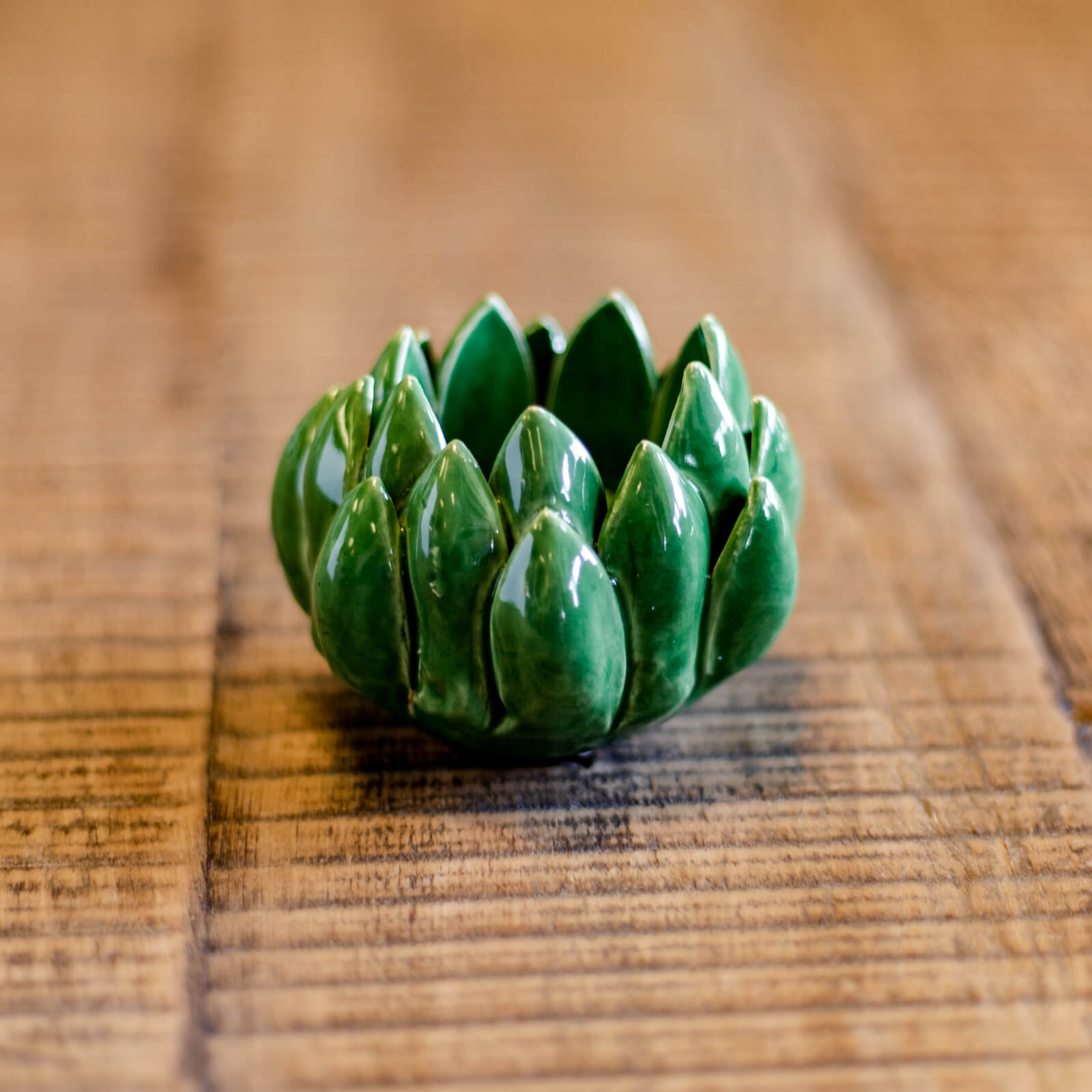 A unique green glazed artichoke shaped ceramic tea light holder rests on a tablescape in Topeka, Kansas near Kansas City