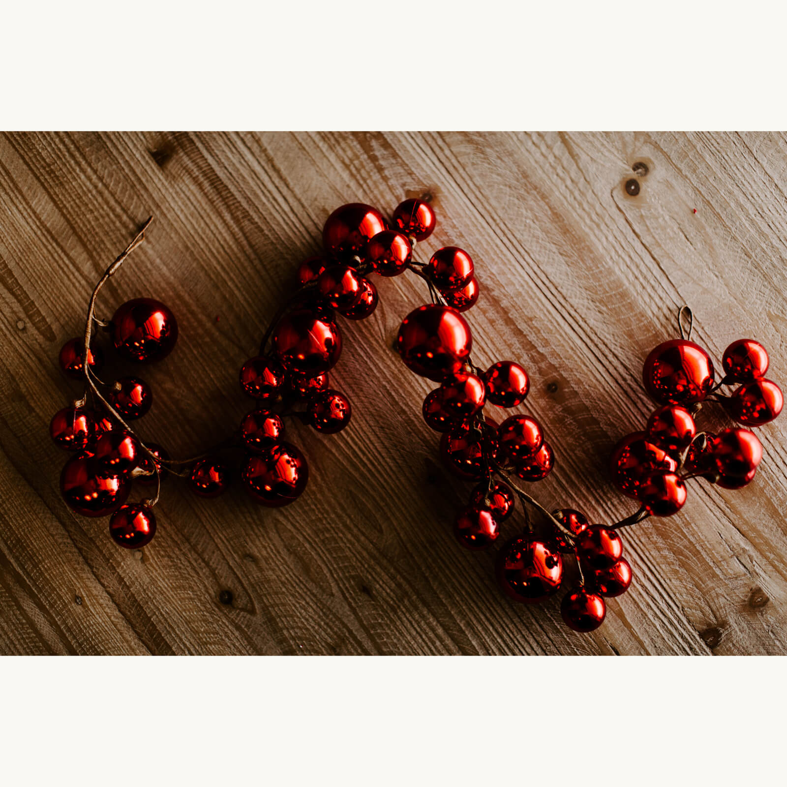 A 4 foot long shiny red ball garland made up of different sized red balls ready for christmas decorating