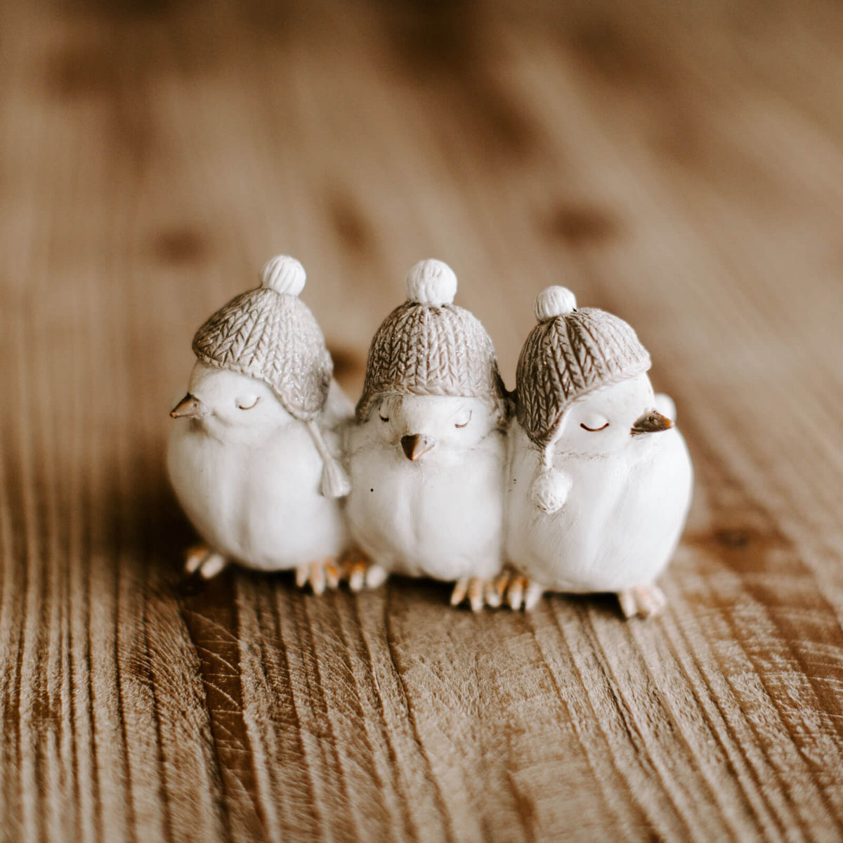 A figurine featuring 3 little white birds in winter stocking caps, with eyes closed