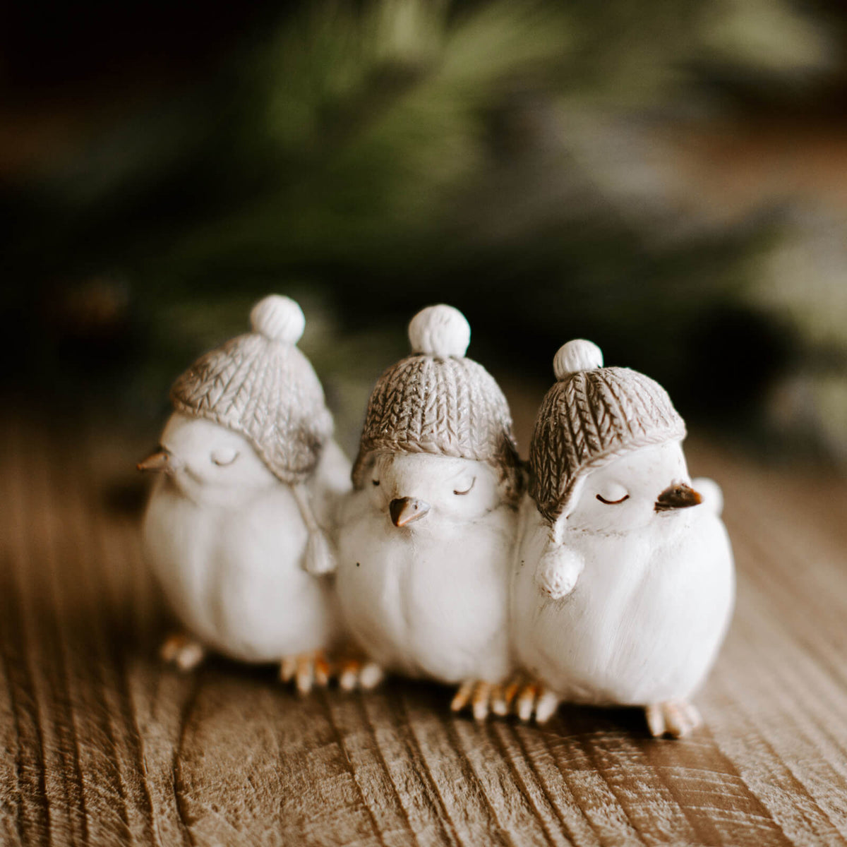 A figurine featuring 3 little white birds in winter stocking caps, with eyes closed resting on a tabletop