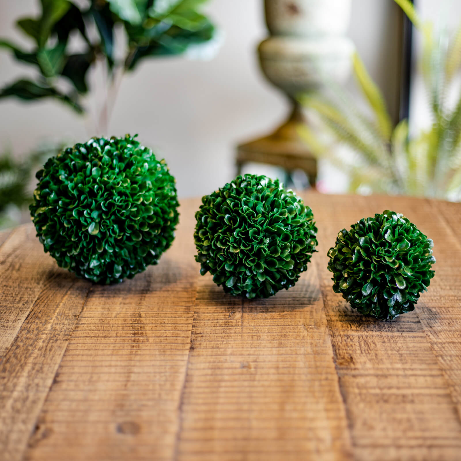 Three different sizes of rich green faux Boxwood balls side-by-side on a living room coffee table in Topeka, Kansas.