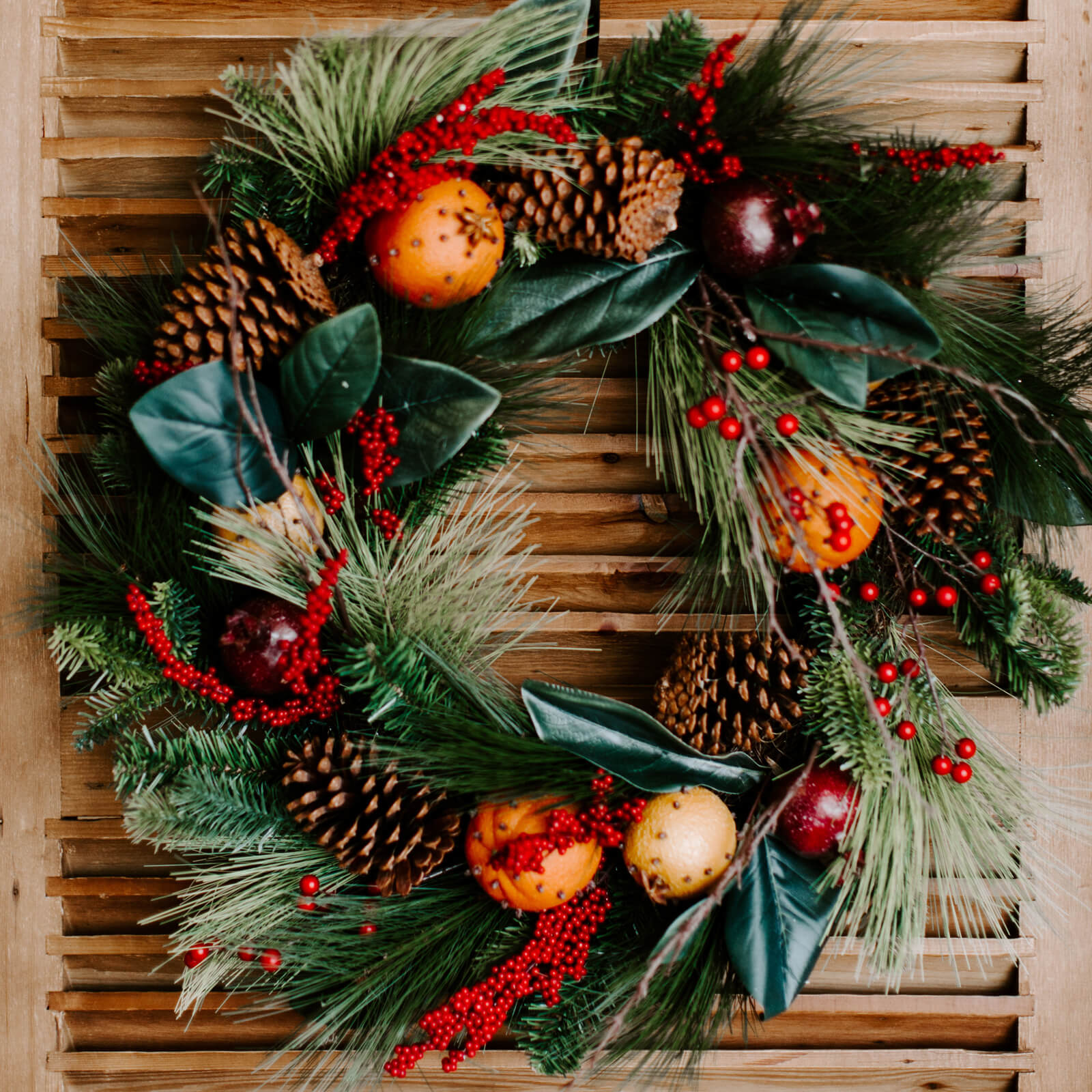 Lush 24 inch diameter wreath with faux magnolia leaves, pine needles, red berry stems, twigs and clover oranges and pomegranates, hung on the front door for Winter decorating