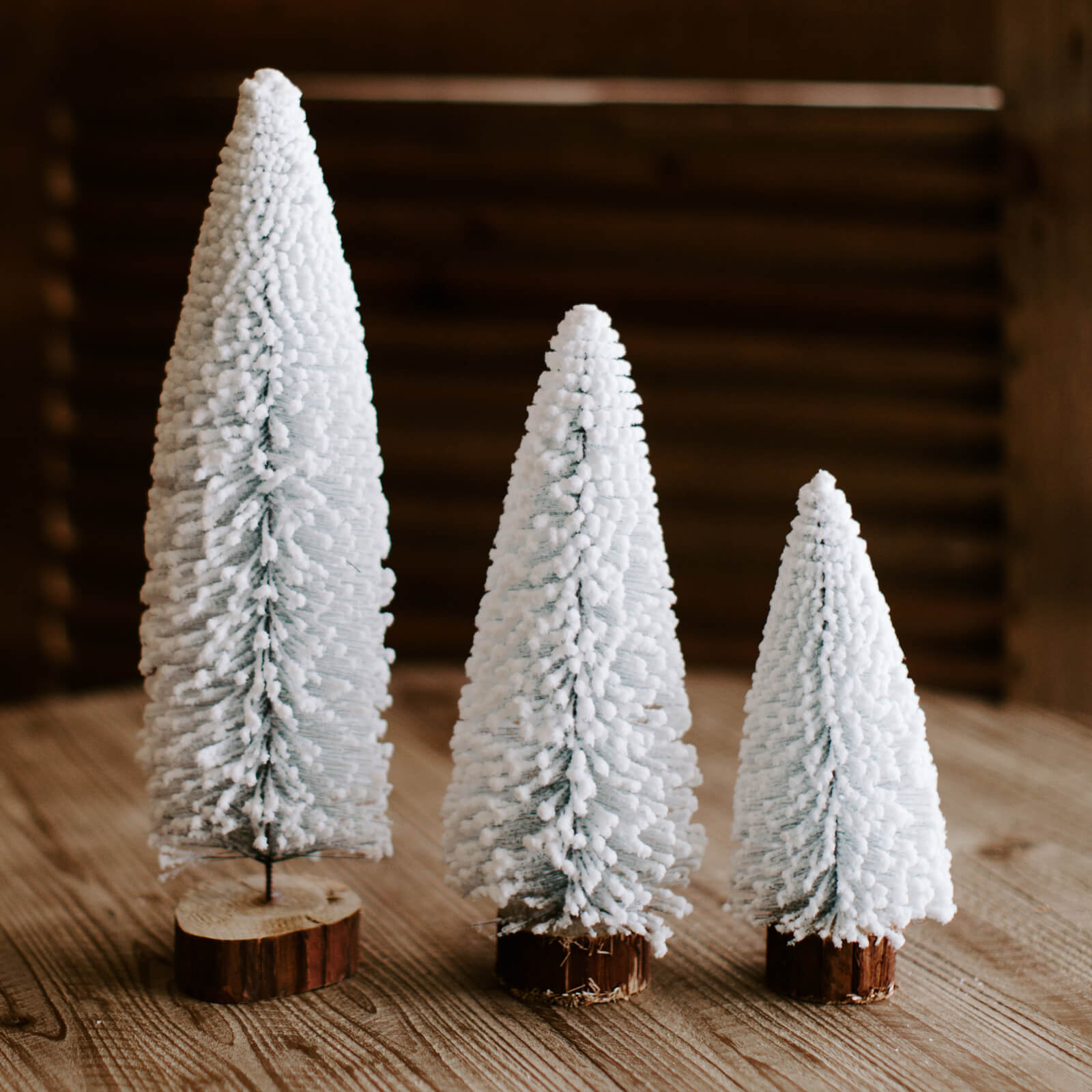 White flocked bottle brush trees with wooden base in 3 different sizes
