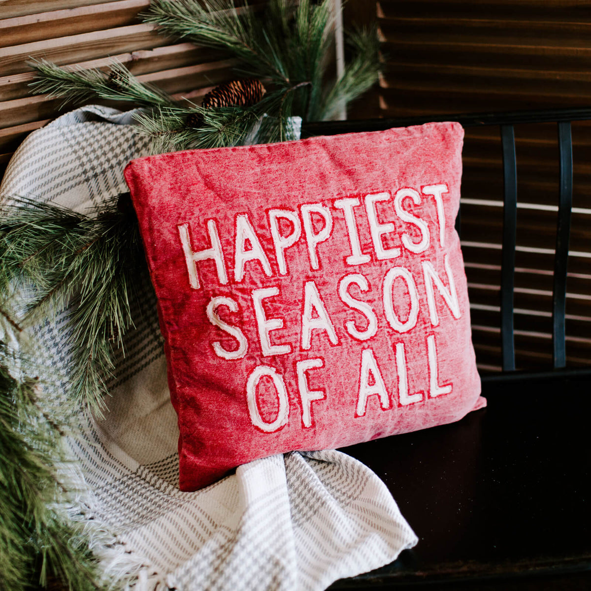 Red washed canvas pillow that reads Happiest Season of All resting on a throw on a bench