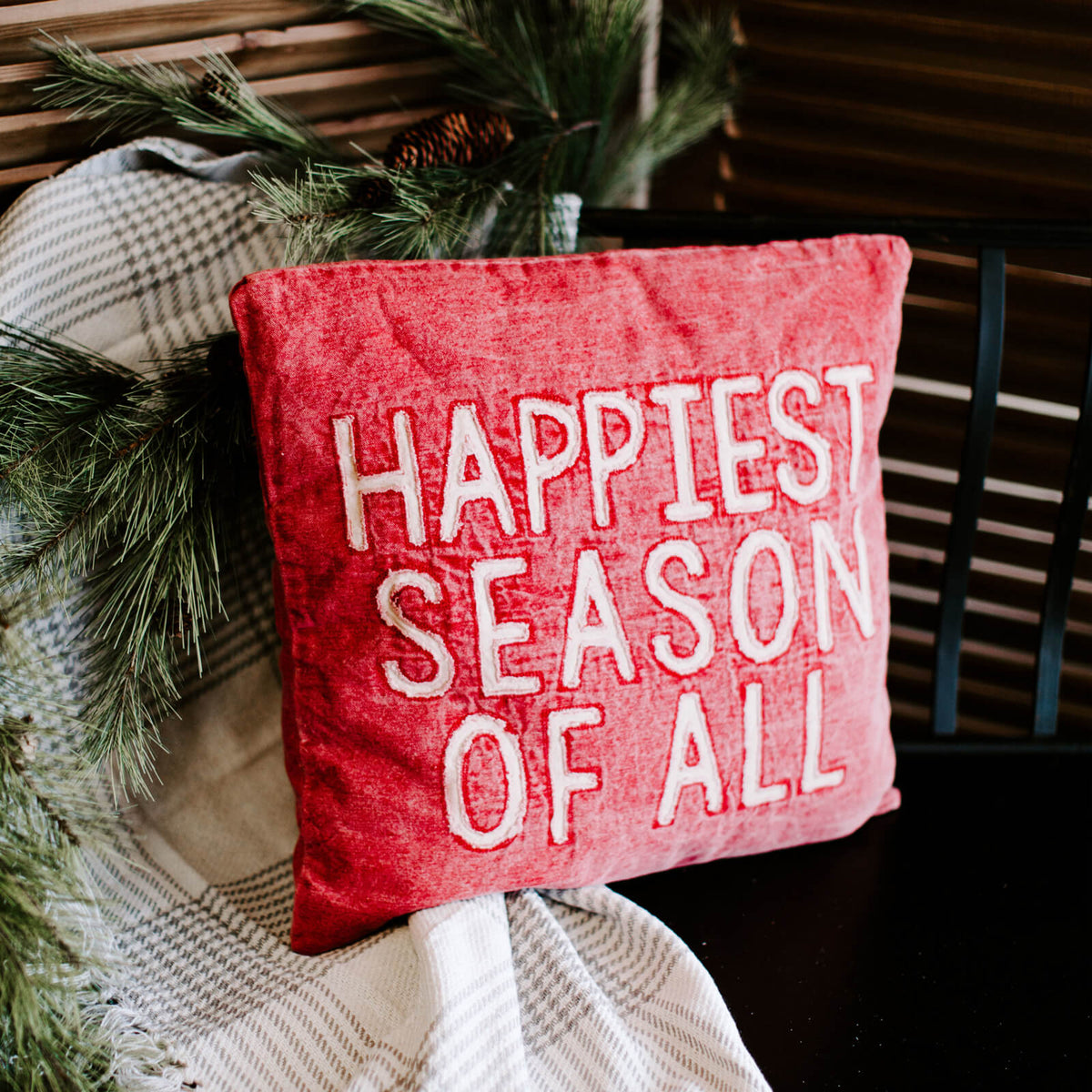 Red washed canvas pillow that reads Happiest Season of All in white, resting on a throw on a bench
