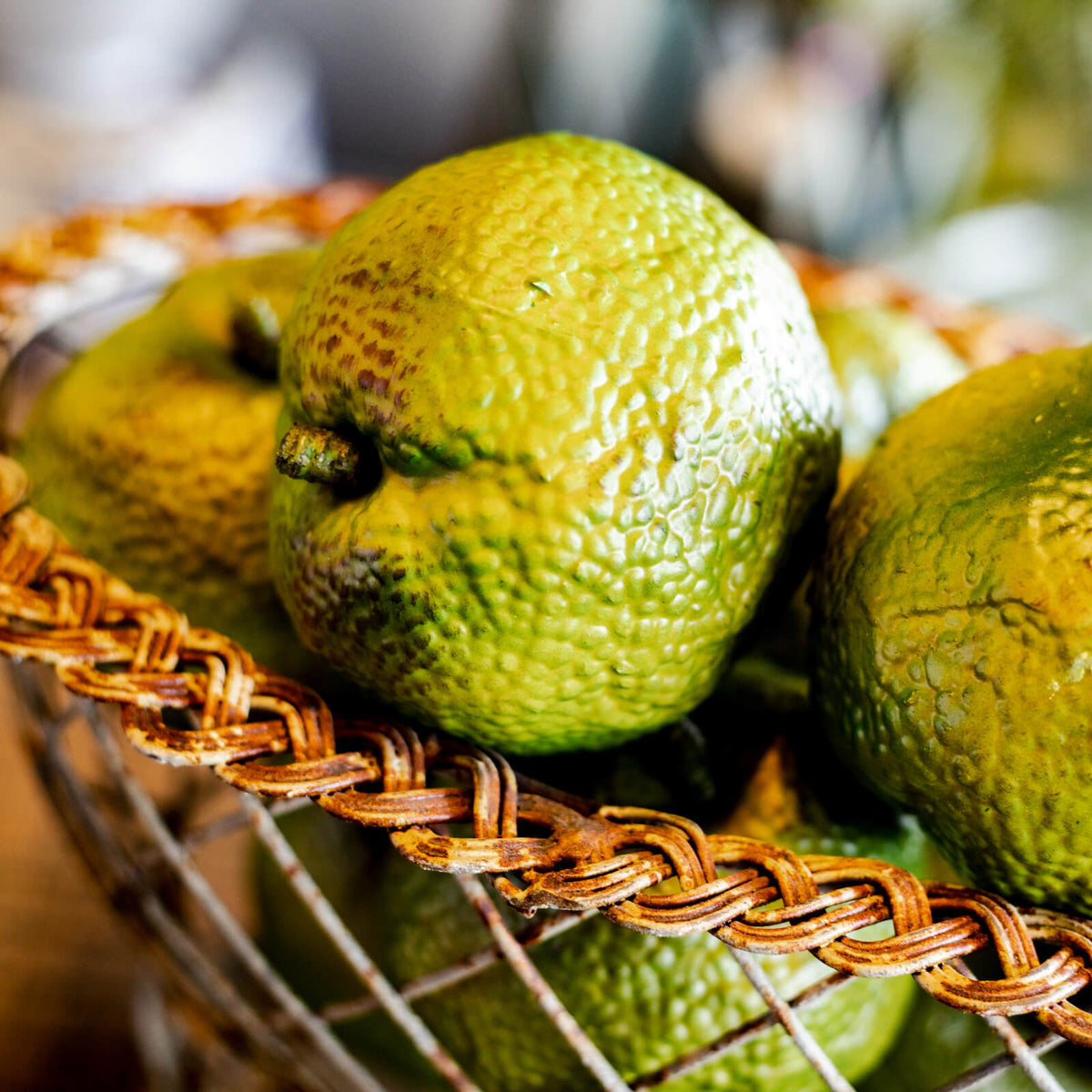 A bowl full of lifelike green hedge apples, resting on a farmhouse table in Topeka, Kansas
