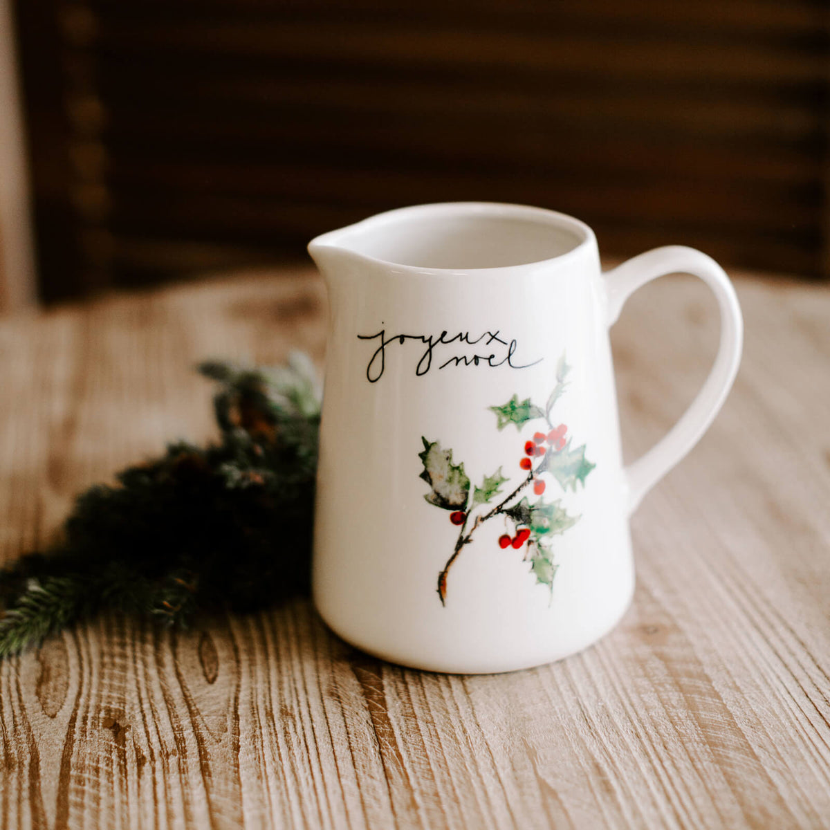 "White stoneware pitcher with painted holly and berry twig with handwritten script ""joyeux noel"" resting on a Christmas dinner table"