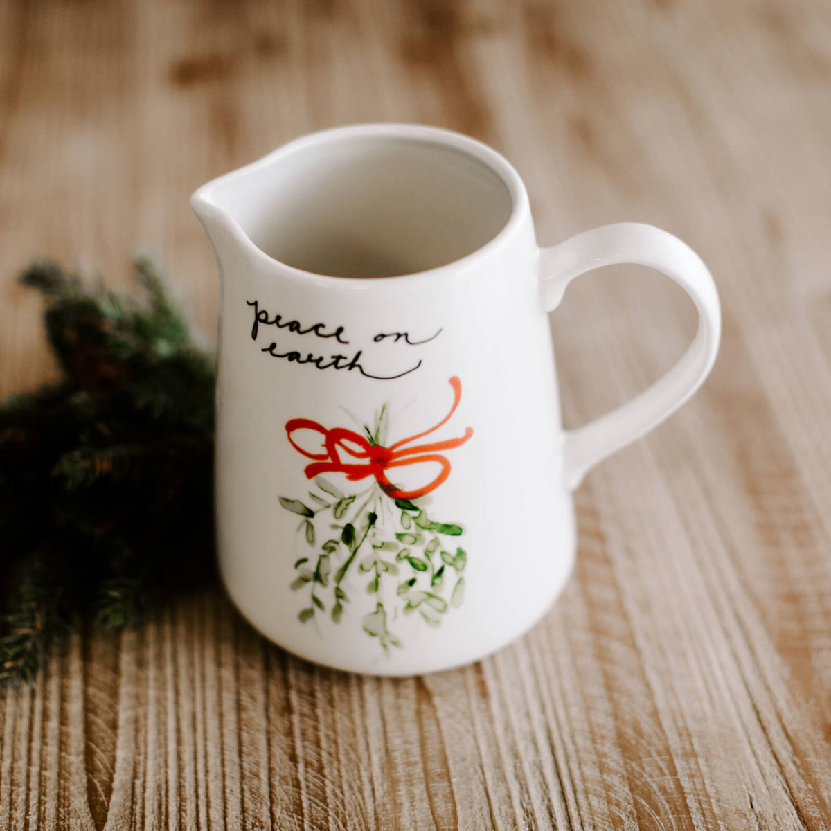 "White stoneware pitcher with painted mistletoe with red ribbon with handwritten script ""peace on earth"" resting on a Christmas dinner table"