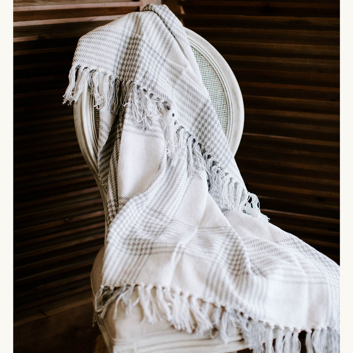 Gray and white houndstooth throw with tassel ends draped over a chair
