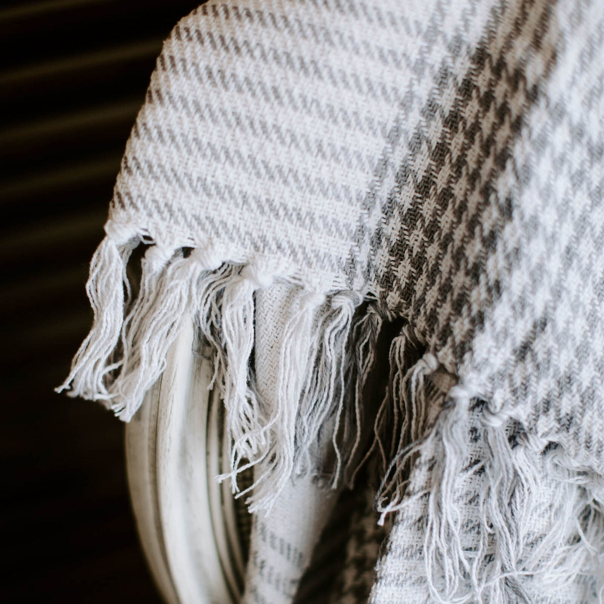 close up detail of a Gray and white houndstooth throw with tassel ends draped over a chair
