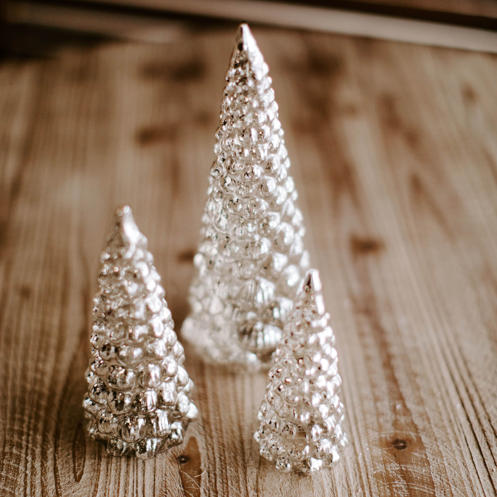 Group of 3 clear and silver mercury glass Christmas trees on a wooden tabletop