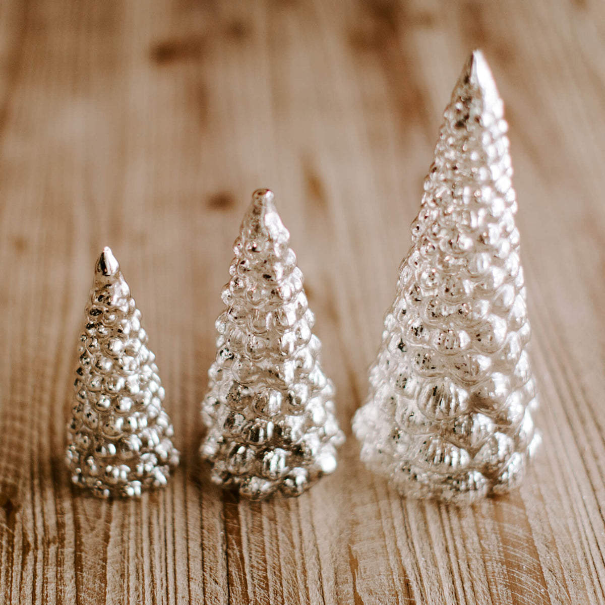 Group of clear and silver mercury glass Christmas trees in 3 different sizes on a wooden tabletop