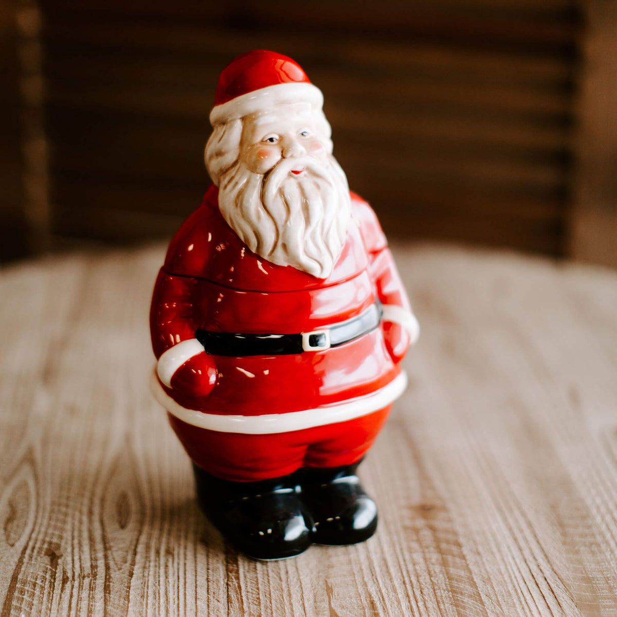 11 and half inch tall stoneware Santa Claus cookie jar in red, black and white, resting on a tabletop