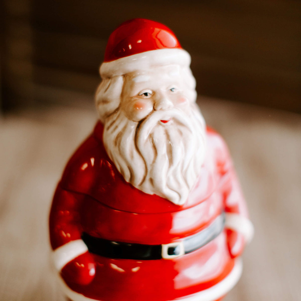 close up detail of an 11 and half inch tall stoneware Santa Claus cookie jar in red, black and white, resting on a tabletop
