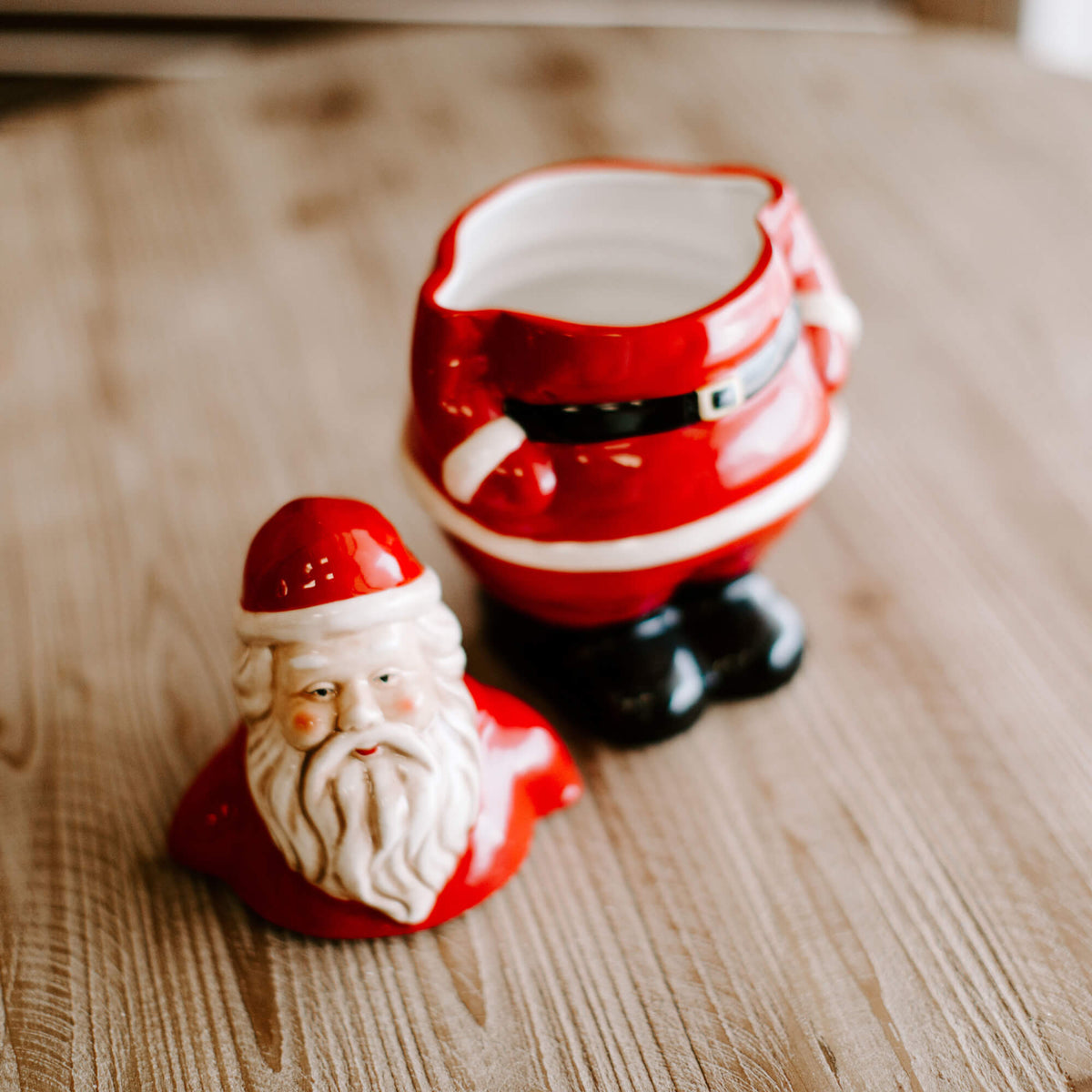 11 and half inch tall stoneware Santa Claus cookie jar in red, black and white, with lid removed resting beside it on the table