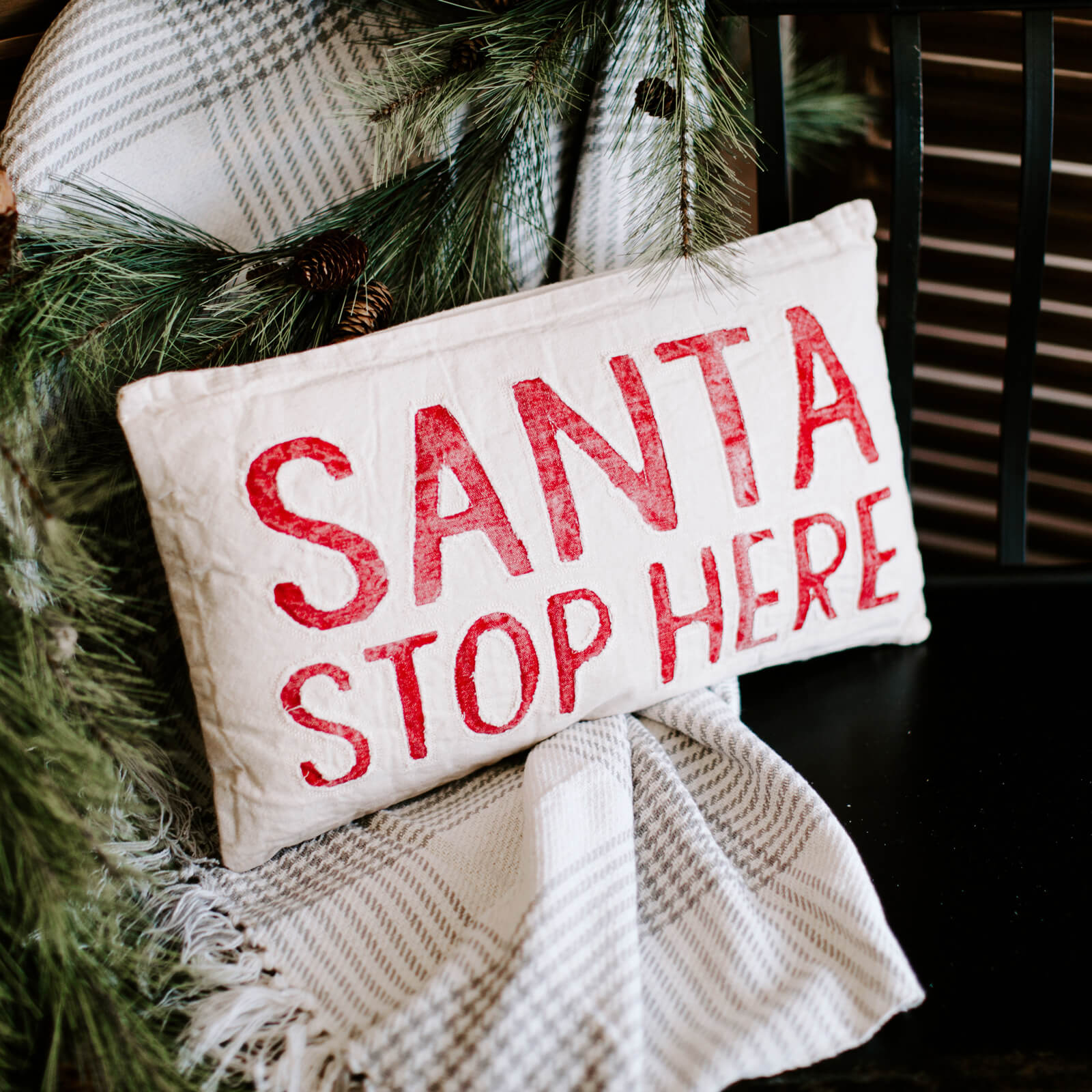 "A washed canvas pillow in white with red lettering that reads ""Santa Stop Here"", resting on a bench with a plaid blanket"