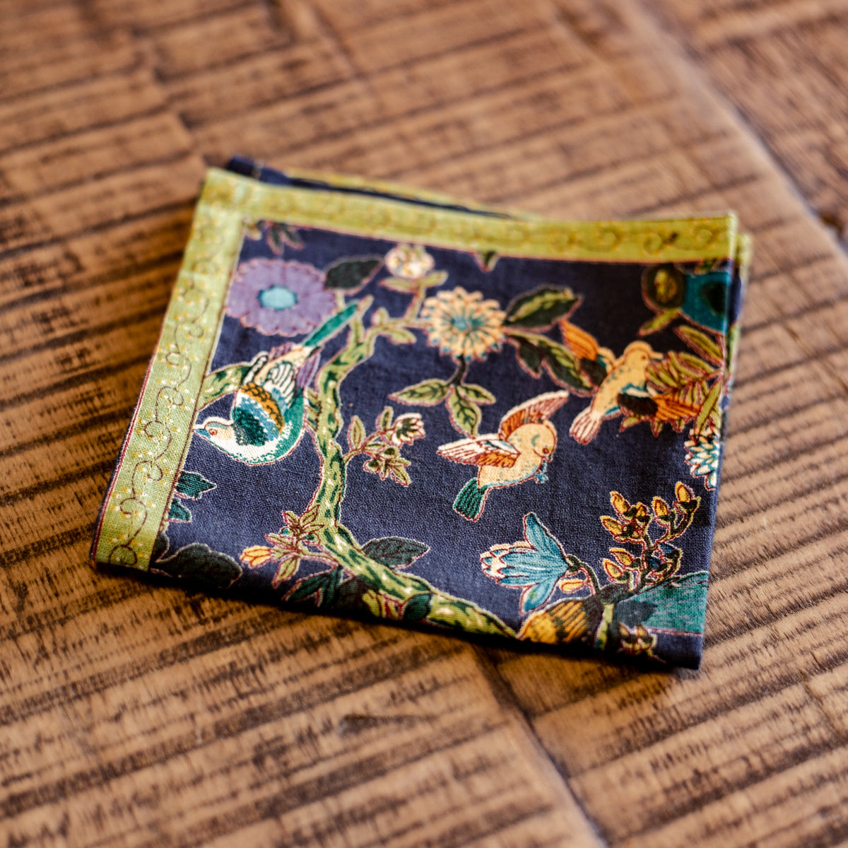 A detailed, colorful cocktail size fabric napkin, featuring richly colored birds and florals, resting on a shabby chic table in Topeka, Kansas.