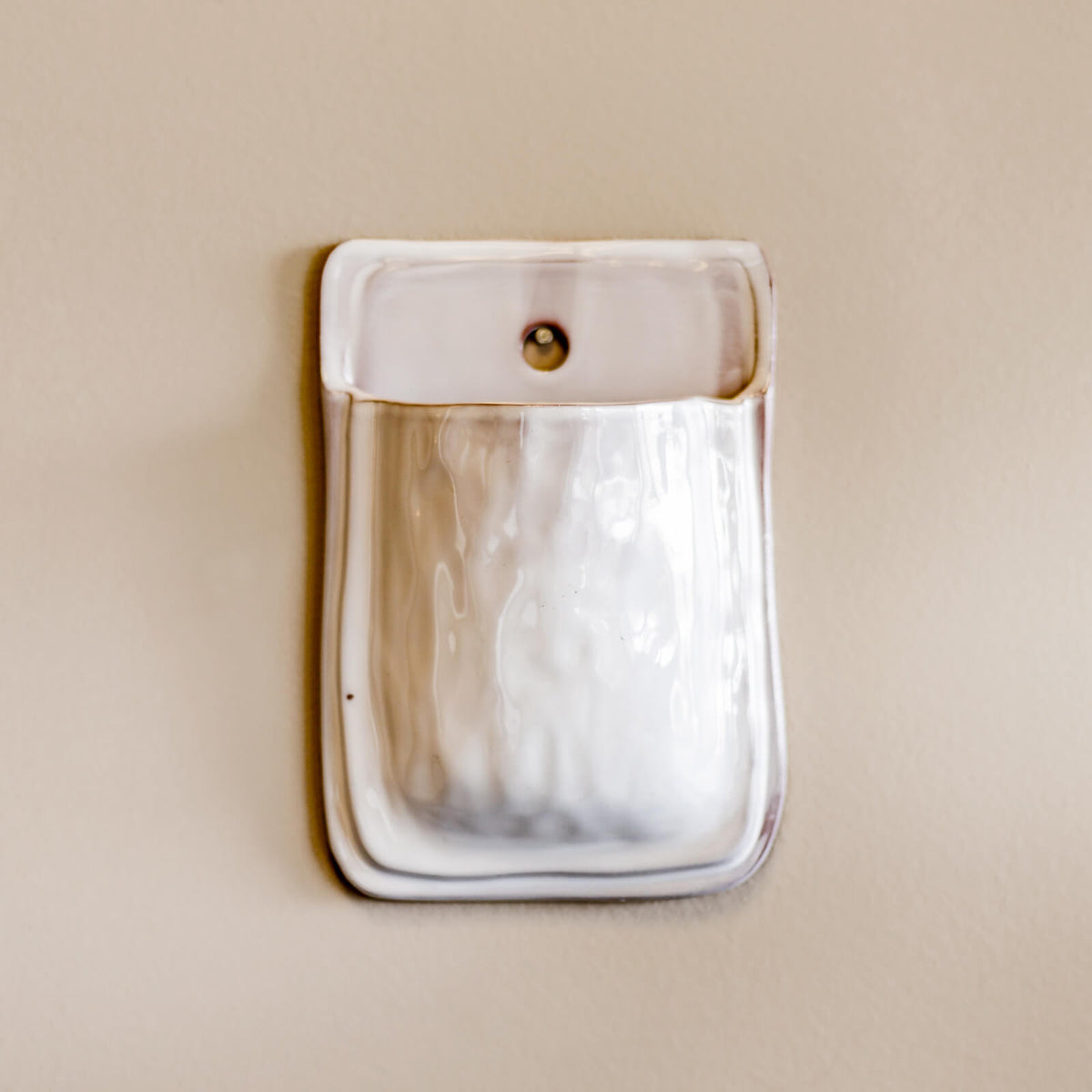 A terracotta pocket planter glazed in white hangs on a nail on a wall, ready for greenery in Topeka, Kansas