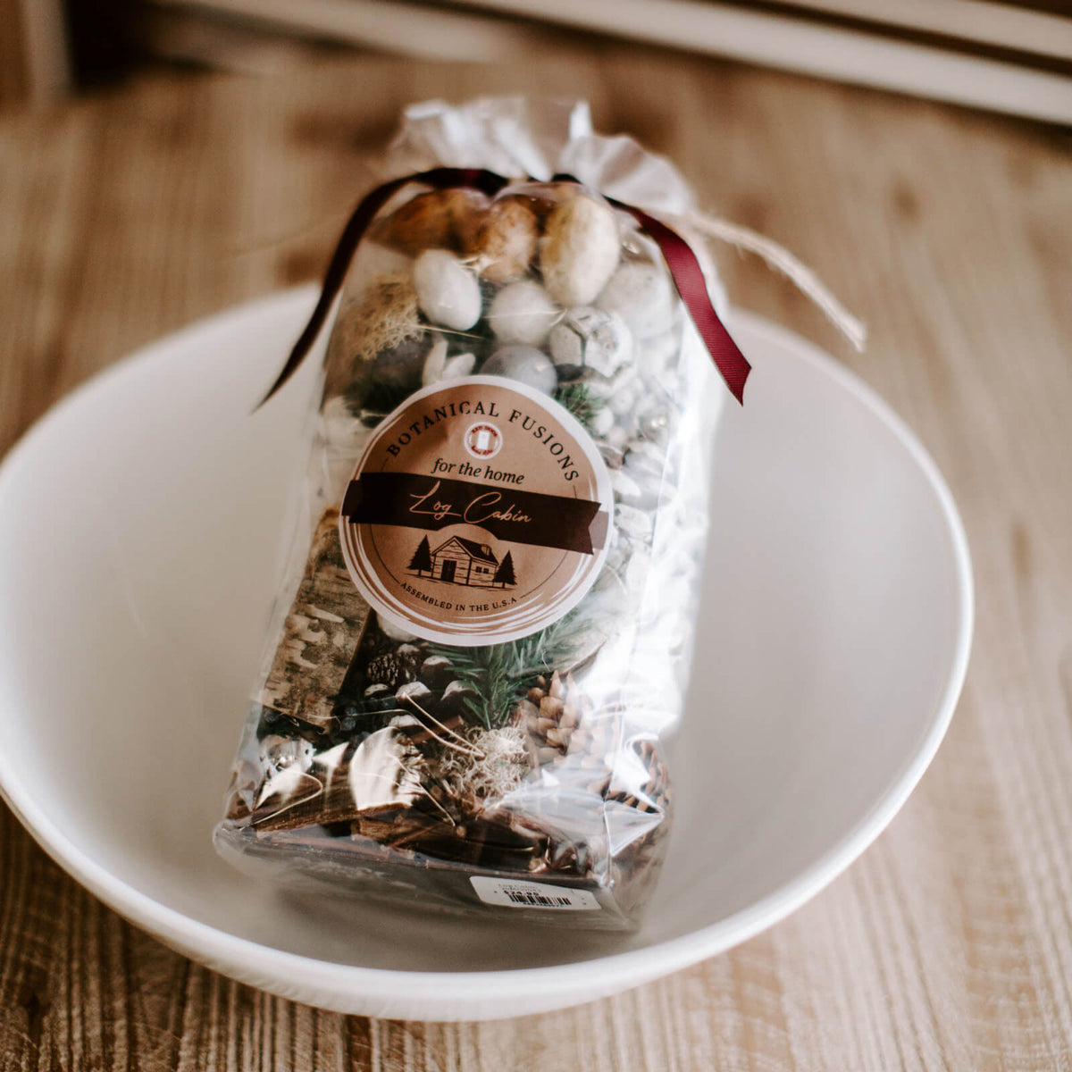 Bag of potpourri in Log Cabin scent resting in a bowl on a table