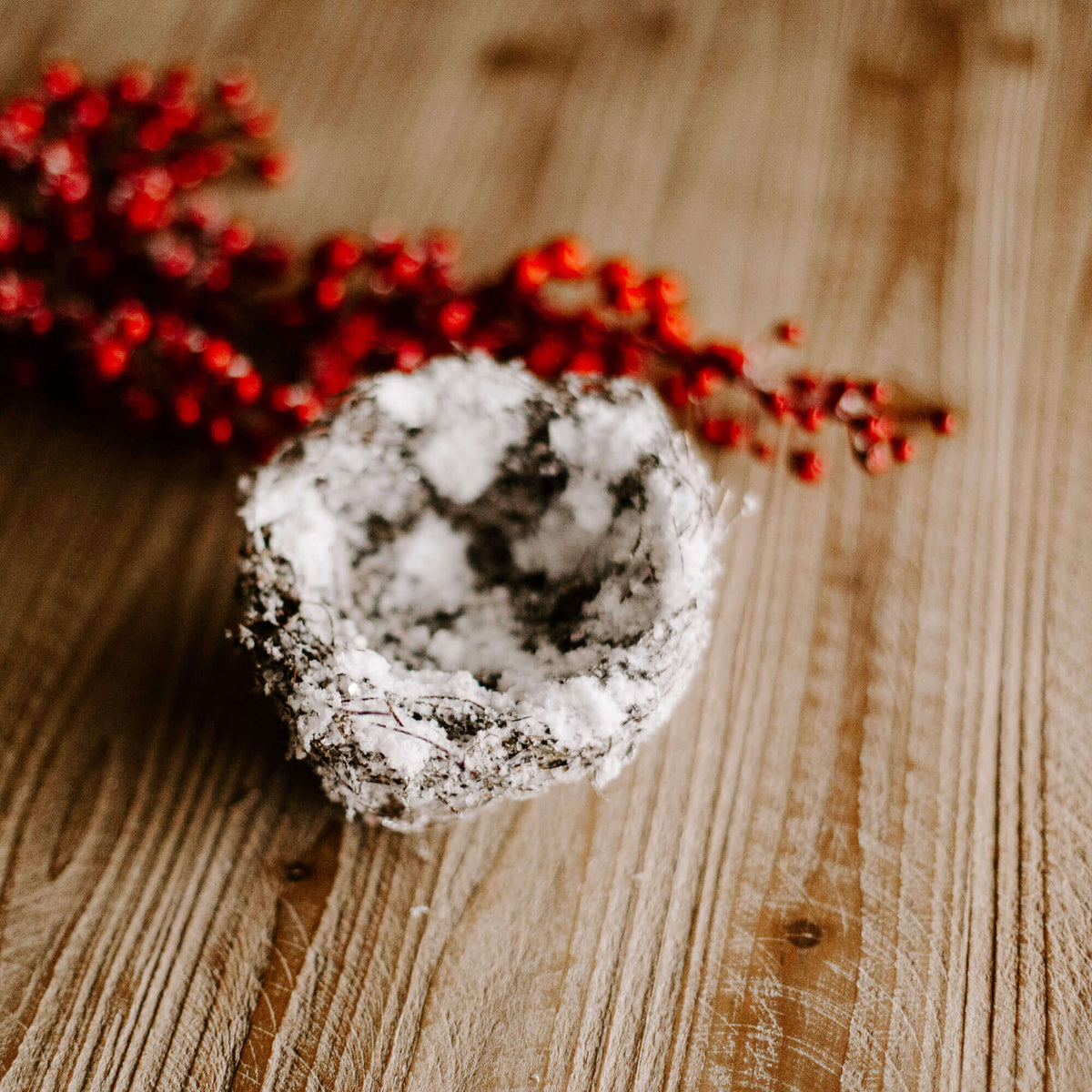 A small four and half inch natural looking bird's nest covered in faux snow for holiday decorating