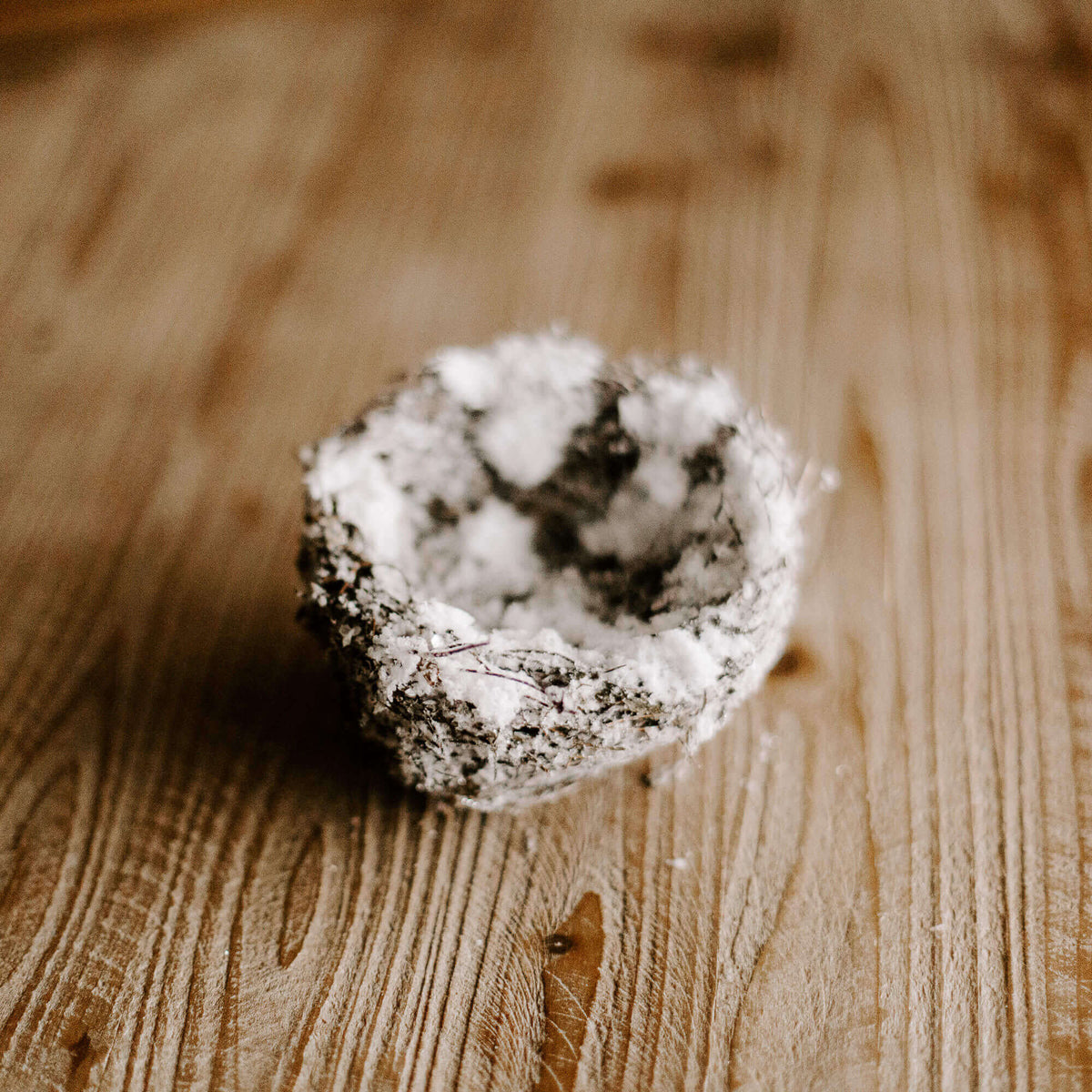 A small four and half inch natural looking bird's nest covered in faux snow for winter decorating