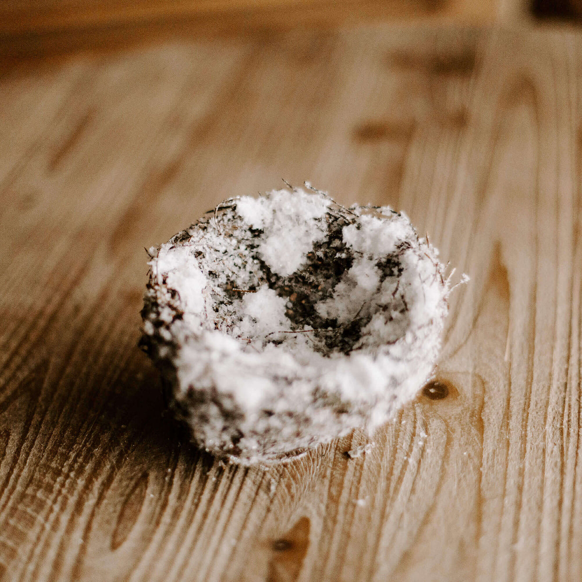 A small four and half inch natural looking bird's nest covered in faux snow for Christmas decorating