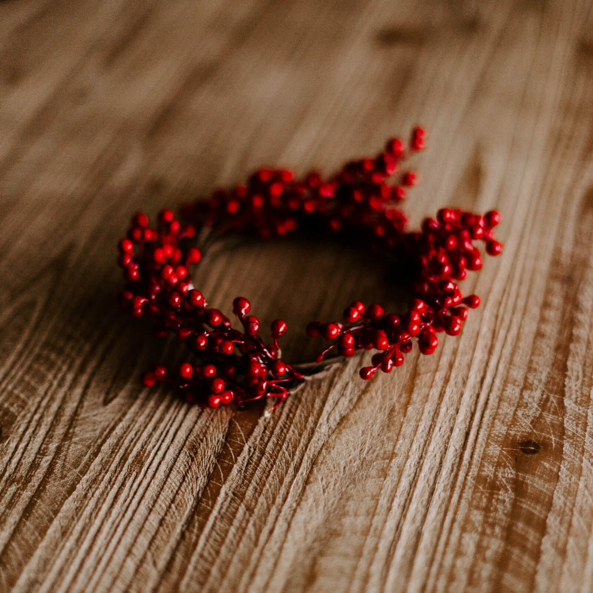 A small four and half inch diameter ring with little shiny red faux berries ready for a Christmas dinner table