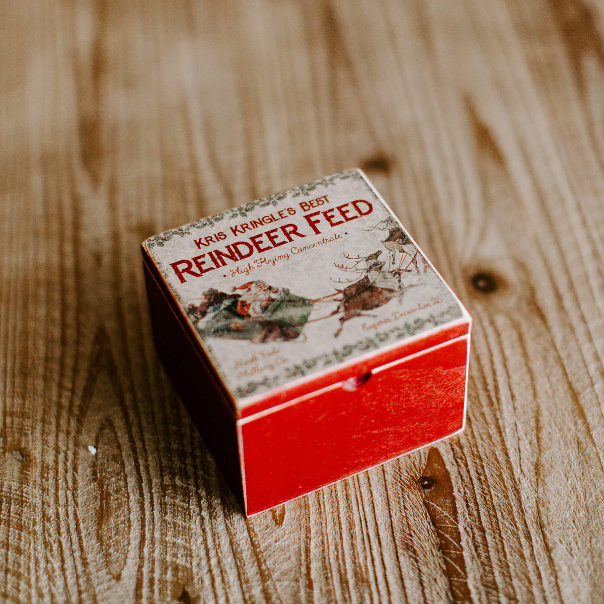 "A vintage looking box with a weathered looking labels that reads ""Kris Kringle's Best Reindeer Feed"""
