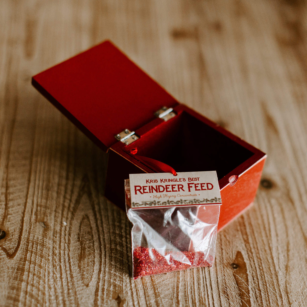 The contents of an old-looking box is a bag of red glitter with the label Kris Kringle's Best Reindeer Feed